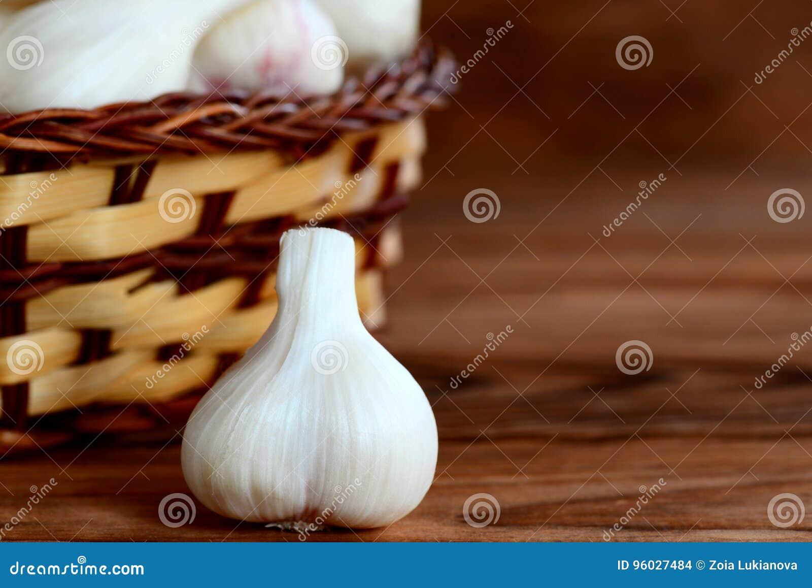 Świeży młody czosnek w koszu na drewnianym tle z kopii przestrzenią dla teksta Przyprawowy czosnku, zdrowego i naturalnego jedzen