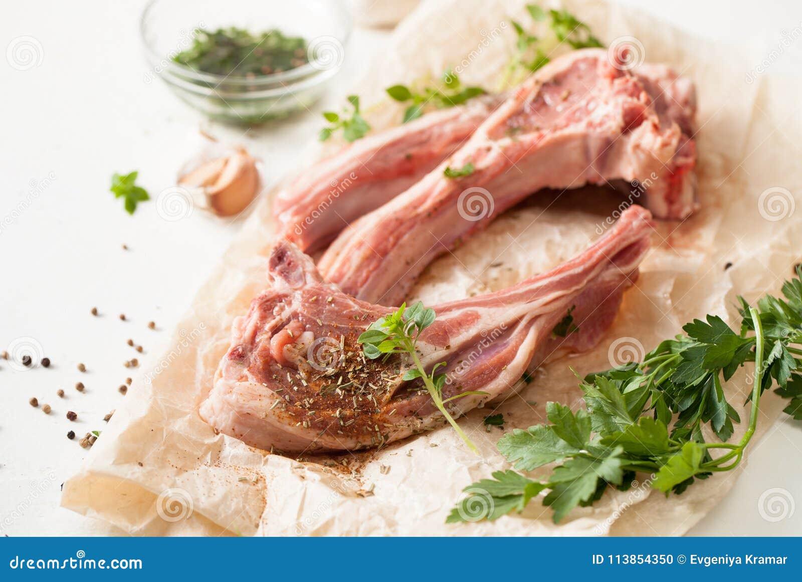 Świeży mięso z pikantność na pieczenie papierze na bielu stole