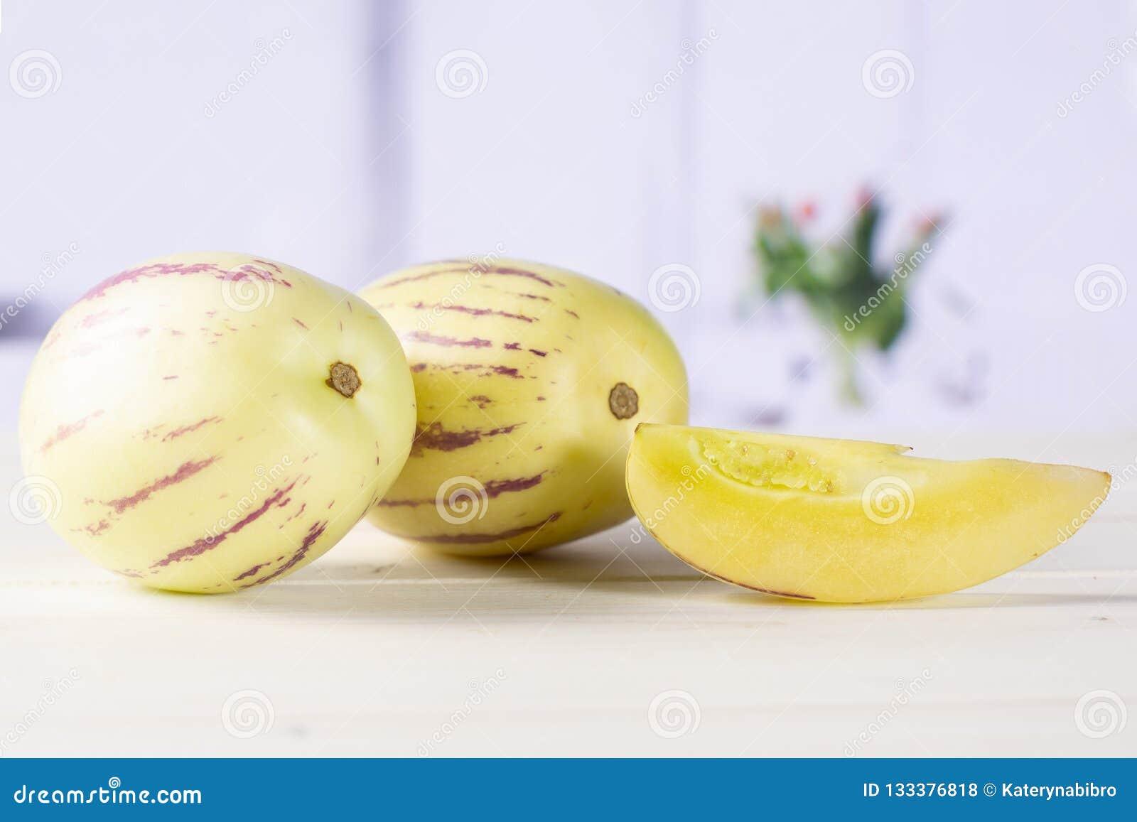 Świeży pasiasty pepino melon z czerwonymi tulipanami
