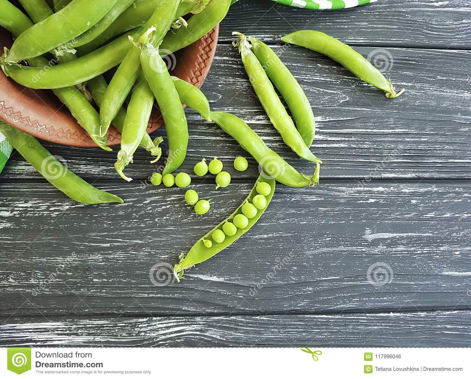 Świeży zielonego grochu naczynie ręcznikowy żniwo składnika lata adry odżywki jarosz na czarnym drewnianym tle