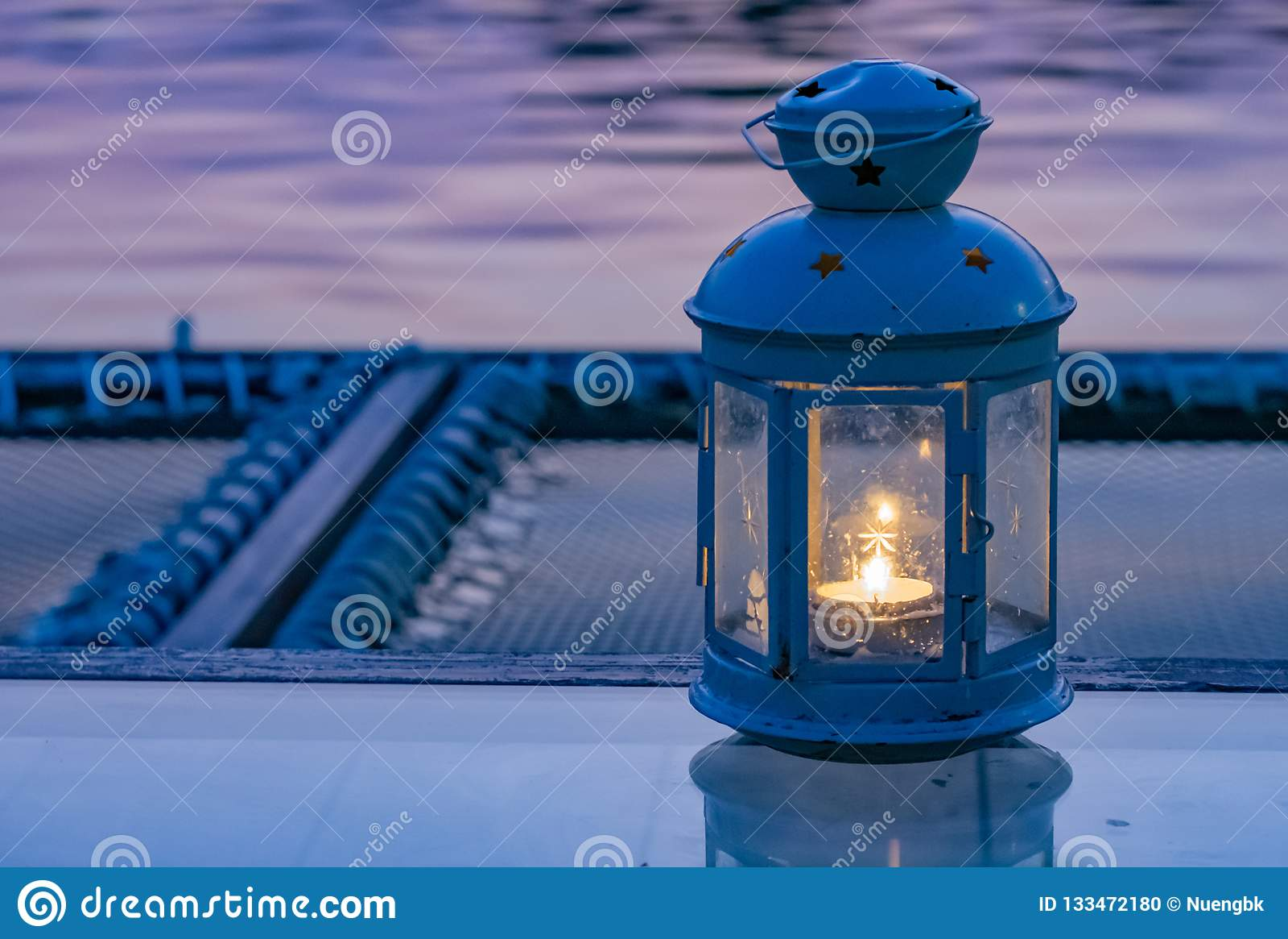 Świeczka ogienie zawierają w lampach na stole, Umieszczać