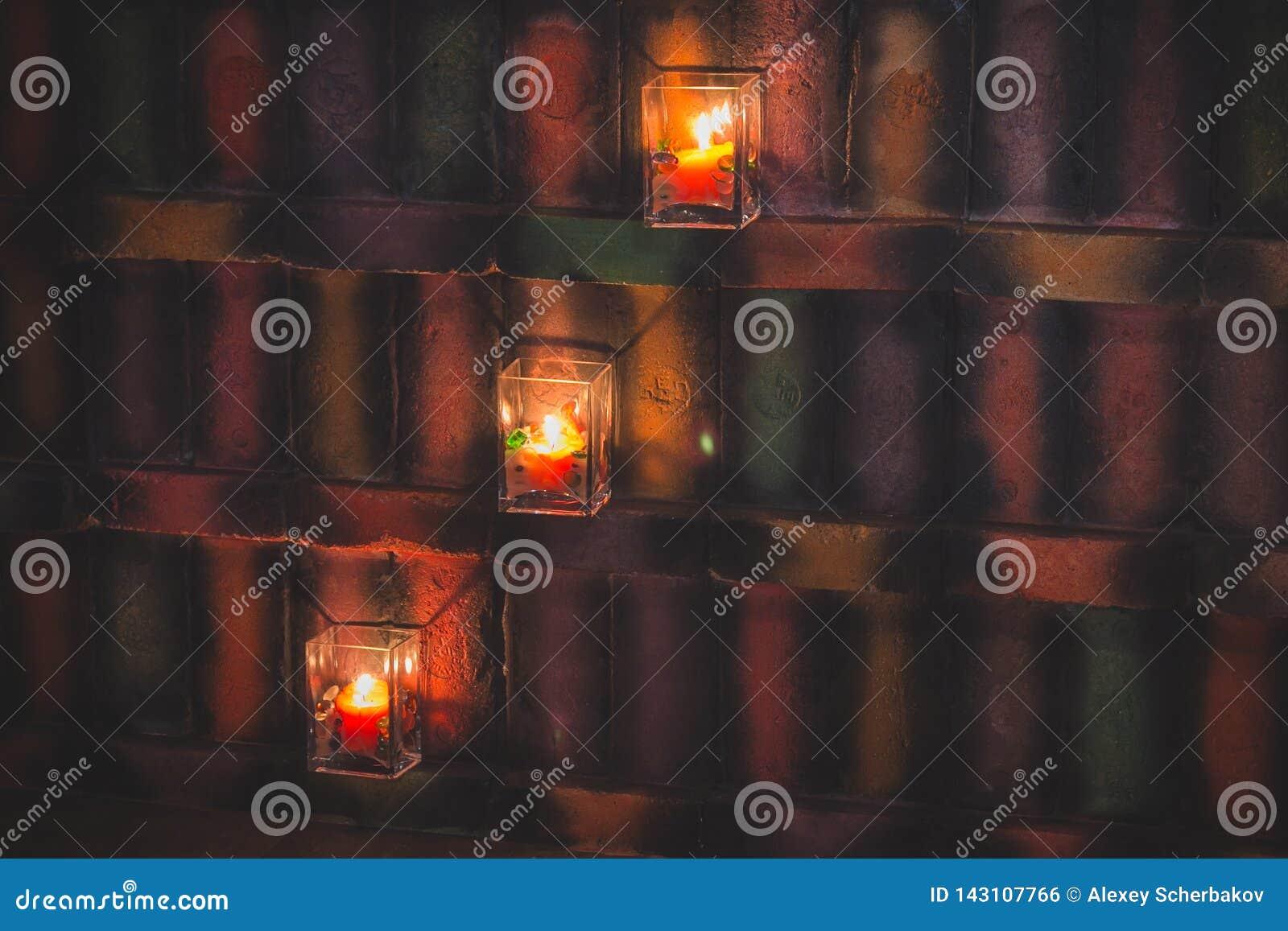 Świeczki w szklanych candlesticks iluminują kolorową ścianę w rocznika stylu