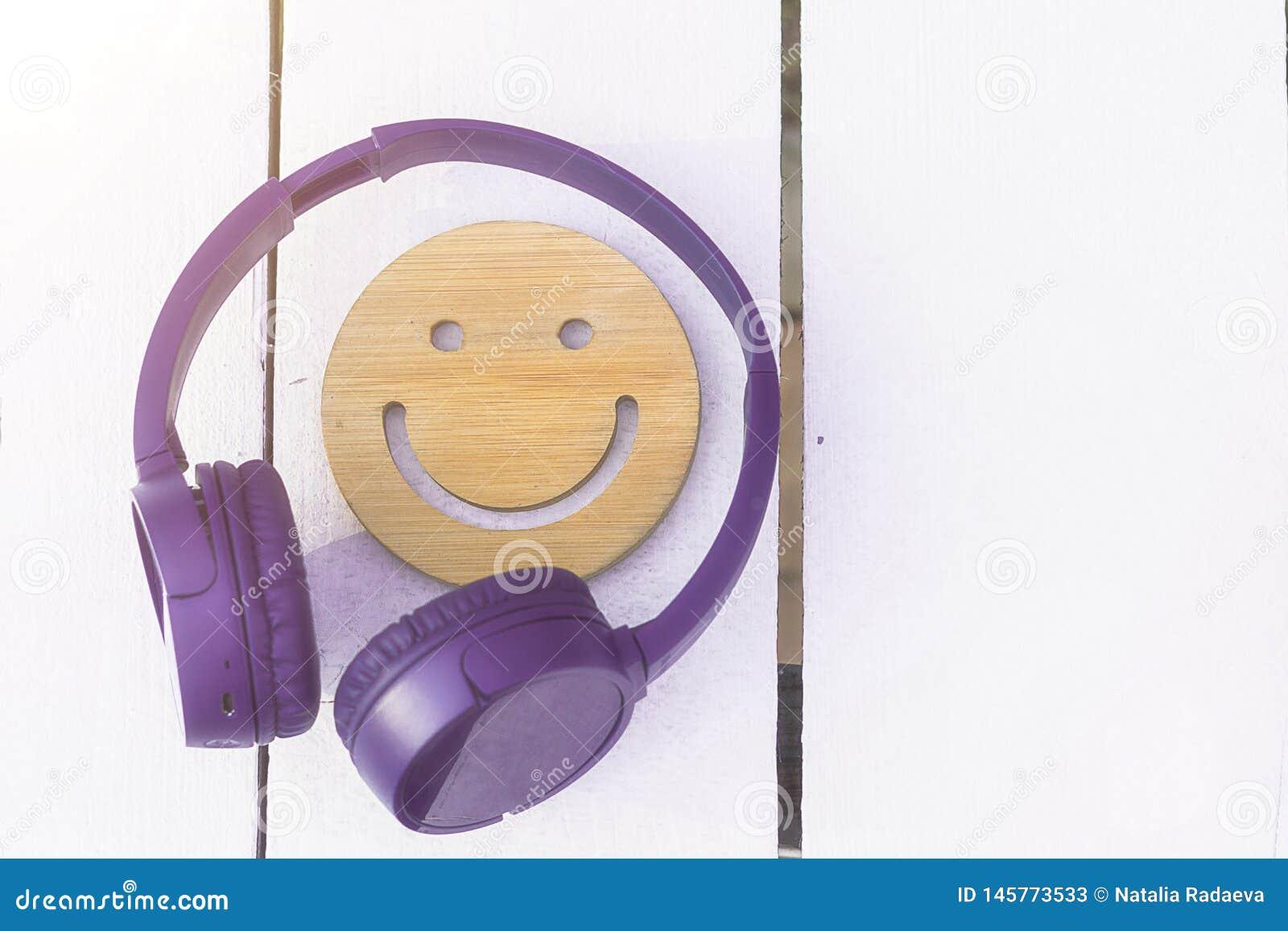 Świetna muzyka dla doskonalić nastroju Bezprzewodowi purpurowi he?mofony i drewniany u?miech na bia?ym tle nowe technologie