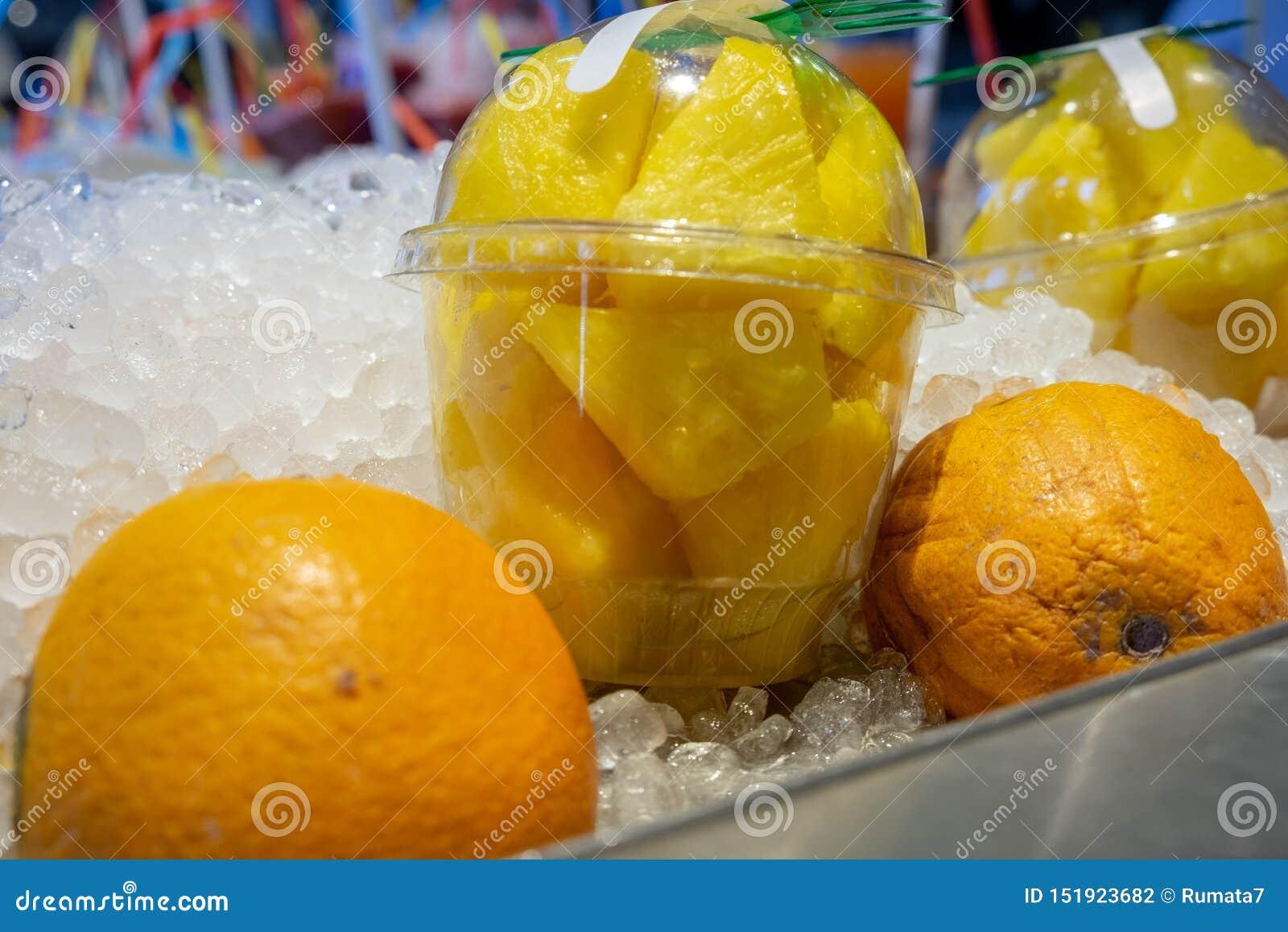 Świezi ananasów kawałki w plastikowych przejrzystych filiżankach i pomarańczach na lodzie dla sprzedaży przy rolnikami wprowadzać