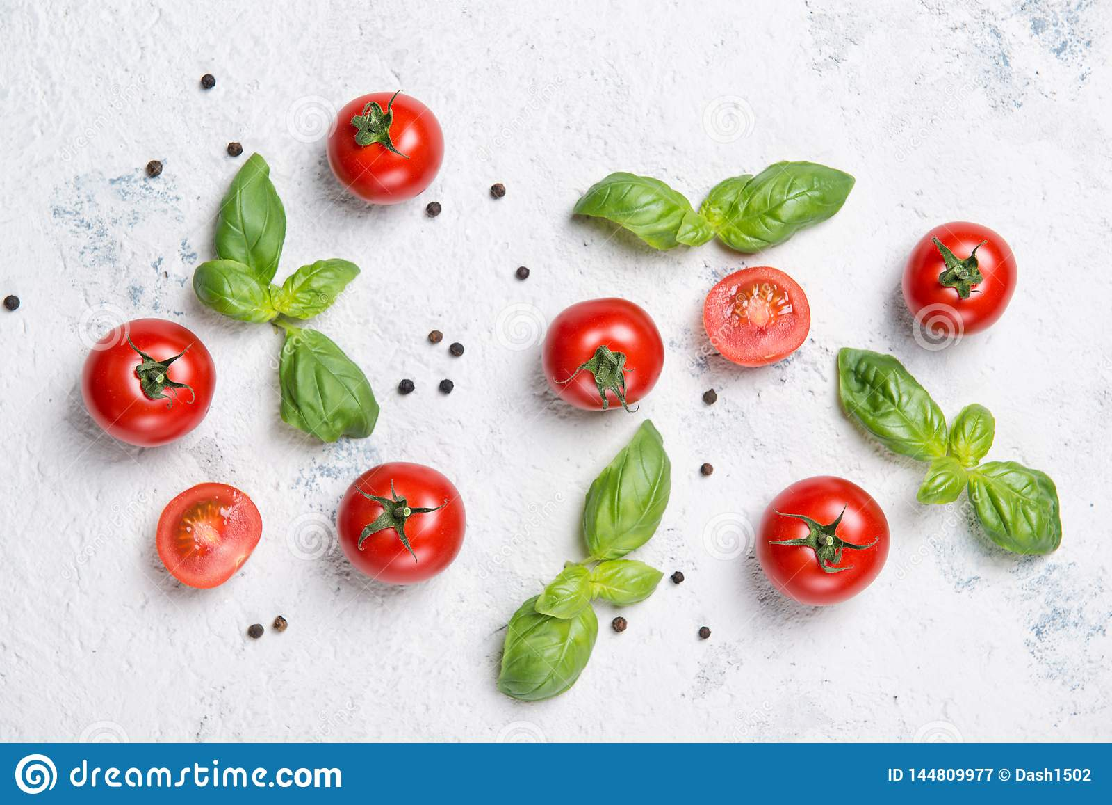 Świezi czereśniowi pomidory z basilów liśćmi i czarnym pieprzem na drylują stół, warzywo wzór, odgórny widok