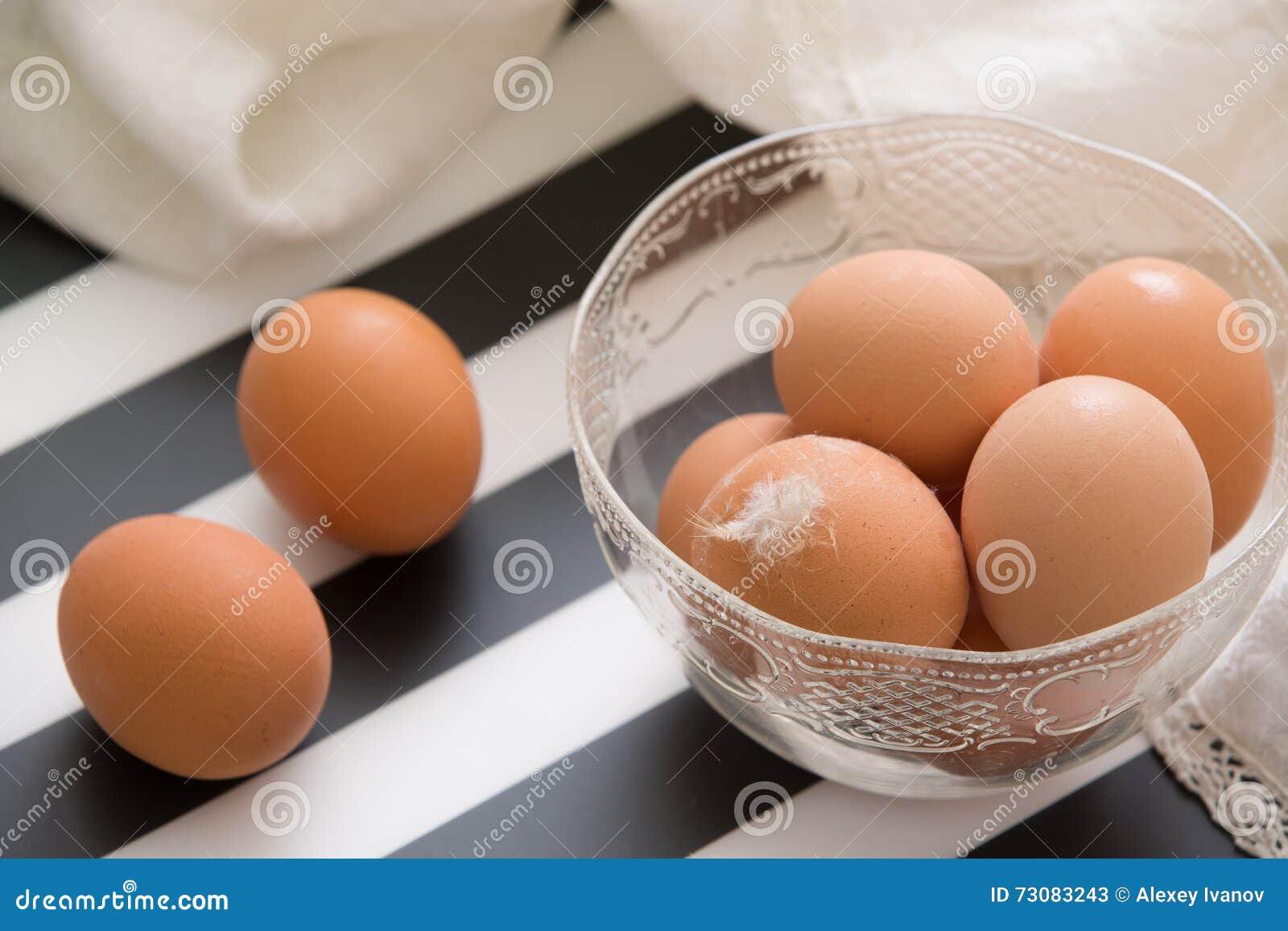 Świezi jasnobrązowi organicznie jajka w cristal pucharze przygotowywającym dla wielkanocy Bielu i czerni lampasy jako backgroubnd
