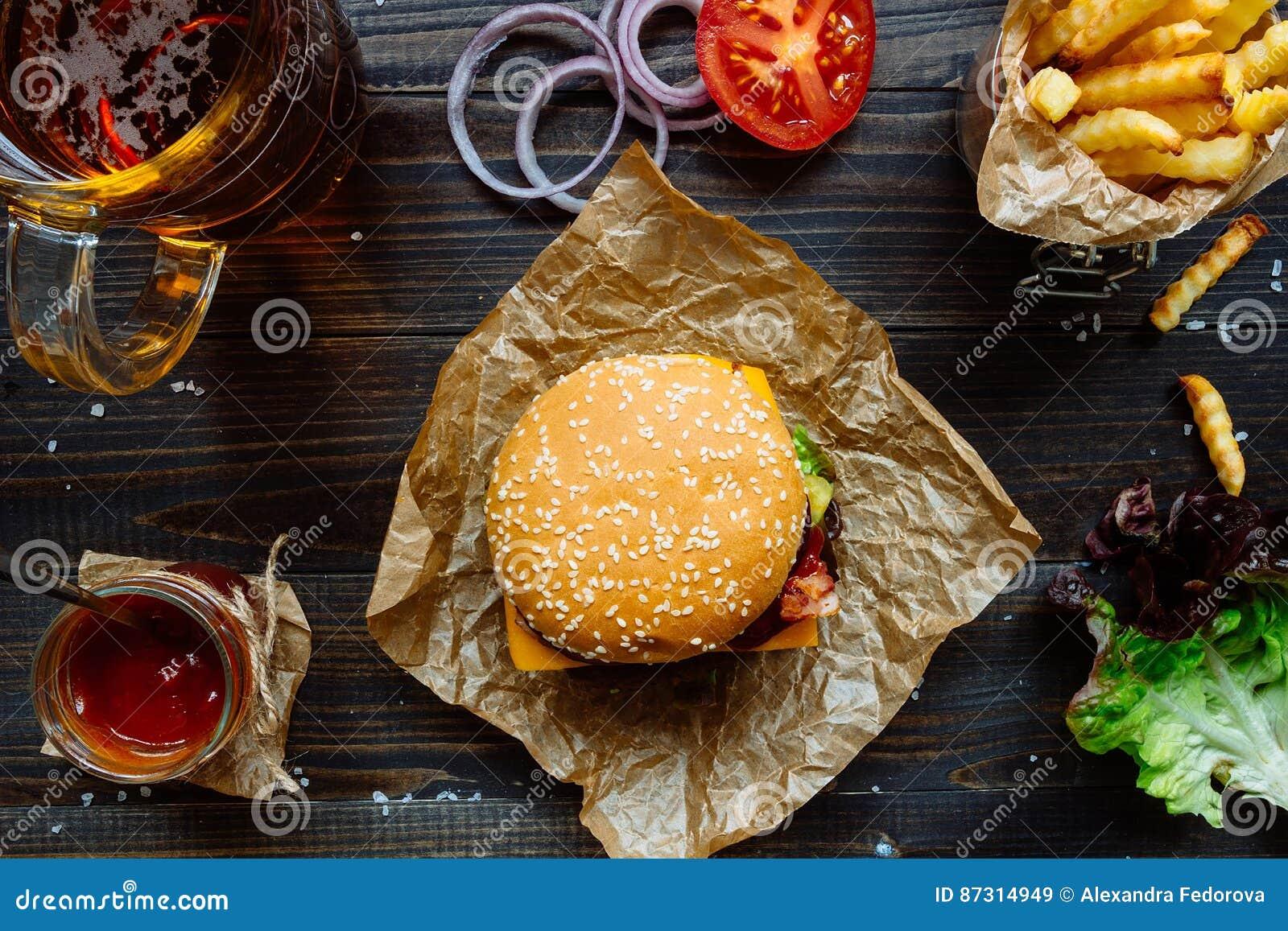 Świezi smakowici hamburgery z francuskimi dłoniakami, kumberlandem i piwem na drewnianym stołowym odgórnym widoku,