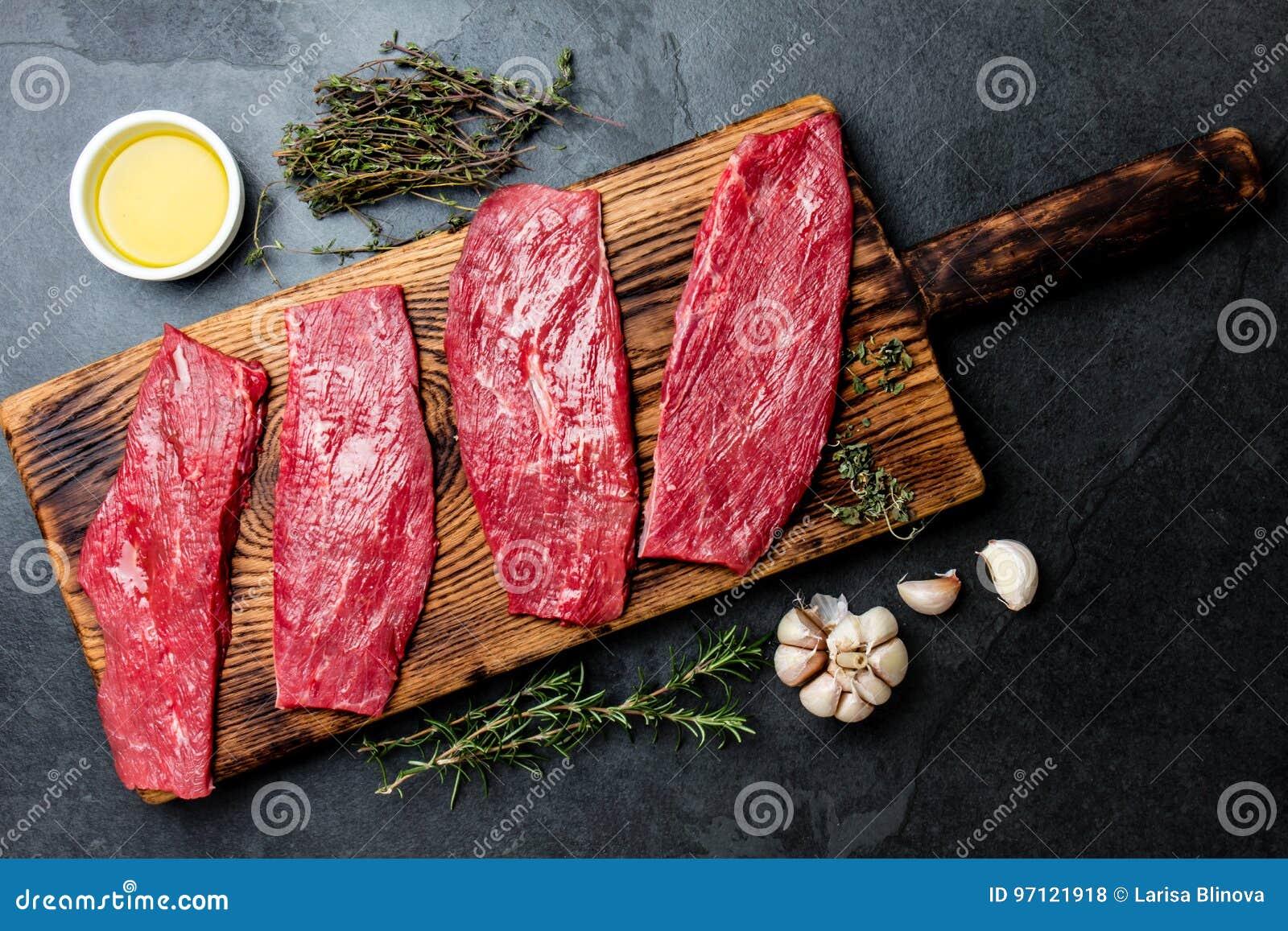 Świezi surowego mięsa wołowiny stki Wołowiny tenderloin na drewnianej desce, pikantność, ziele, olej na łupkowych szarość tle Kar