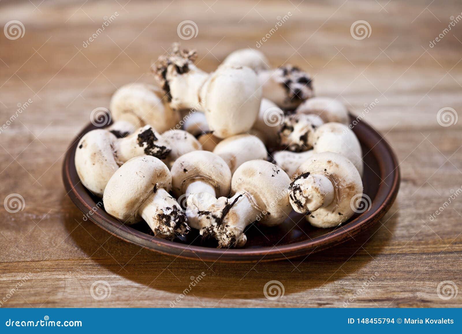 Świezi surowi organicznie szampiniony na brązu ceramicznym talerzu na drewnianym stole