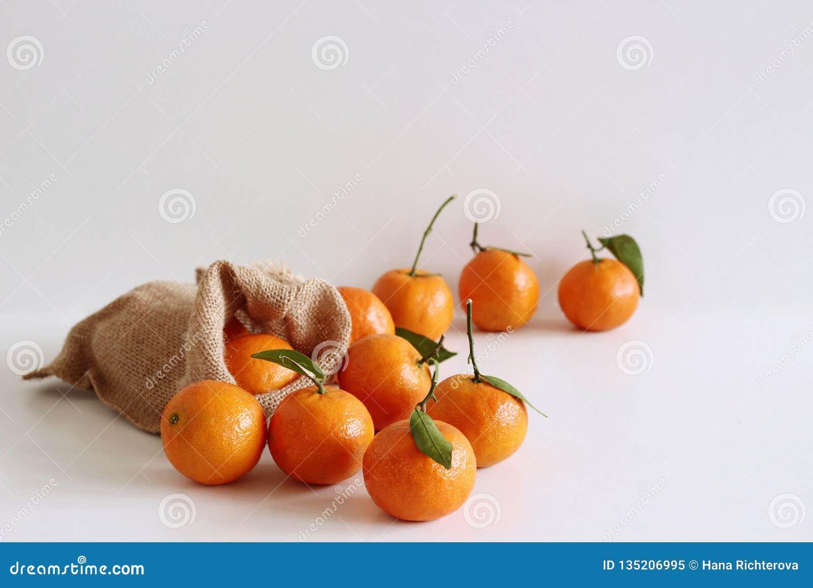 Świezi surowi organicznie Tangerines z zielonymi liśćmi w torbie na białym drewnianym stole kosmos kopii Bogactwo odżywki, włókno