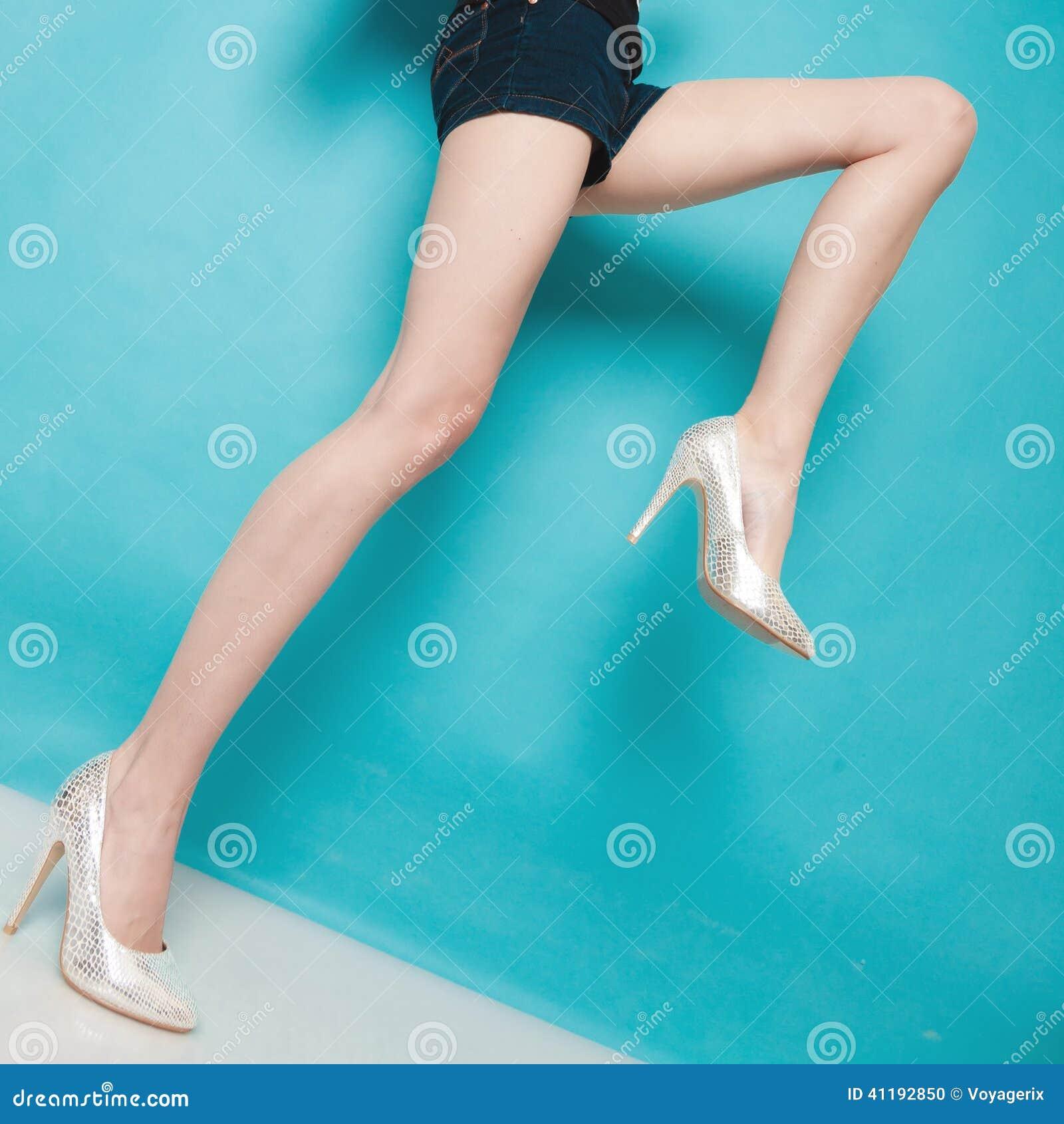 在性感的腿的银色高跟鞋