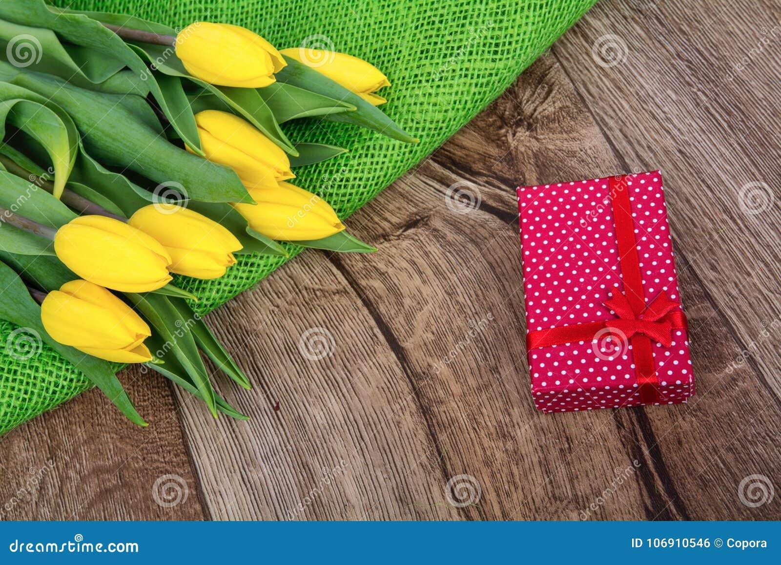 Żółci tulipany i prezent na drewnianym stole