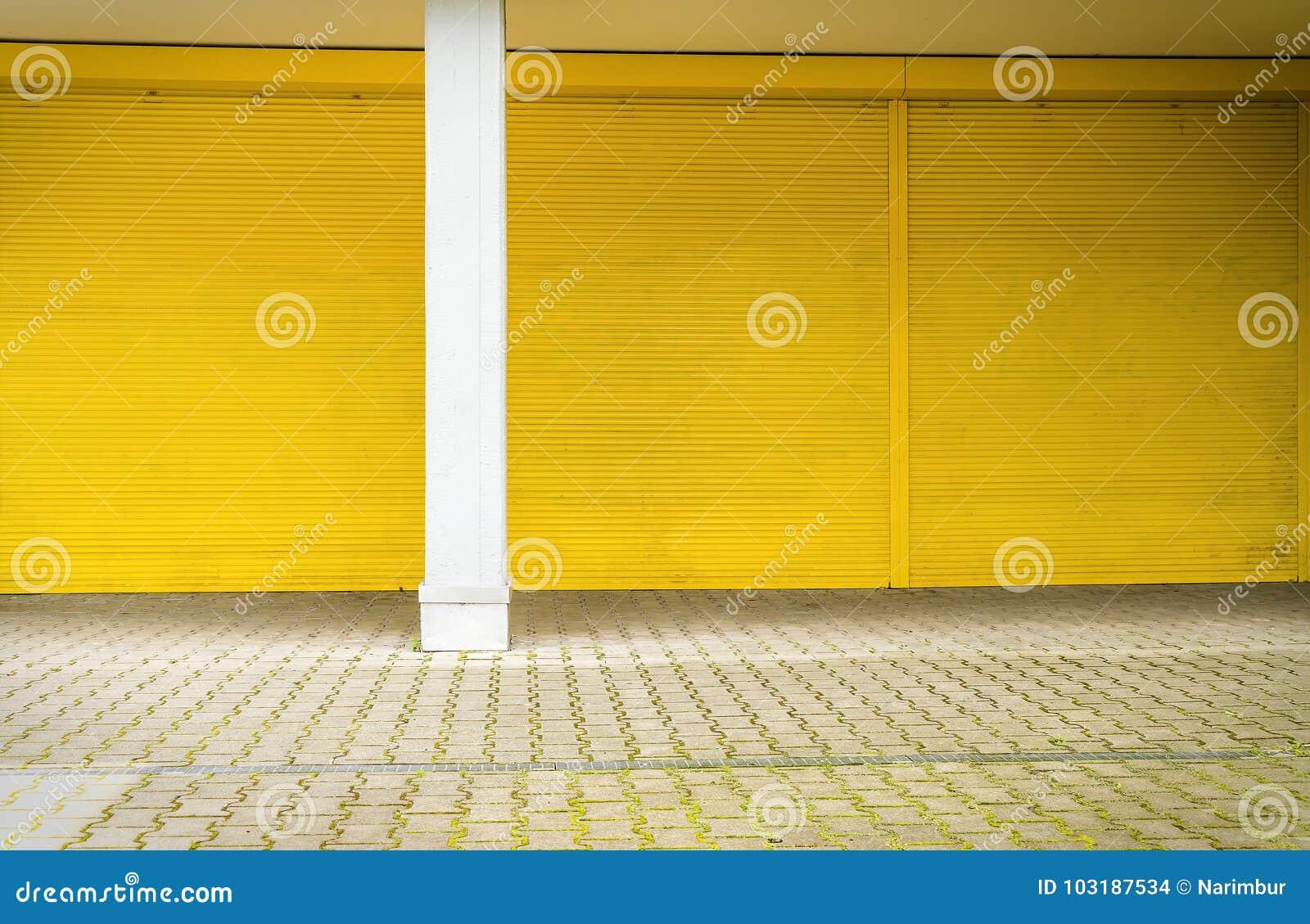 Żółta rolkowa żaluzja i bruk