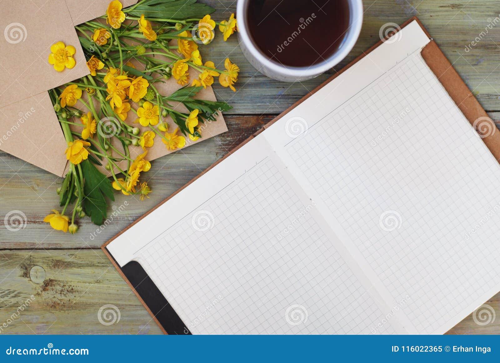 Żółtego Małego kwiat Herbacianej filiżanki Otwartego notatnika tła Kopertowy Nieociosany Drewniany mieszkanie Lay