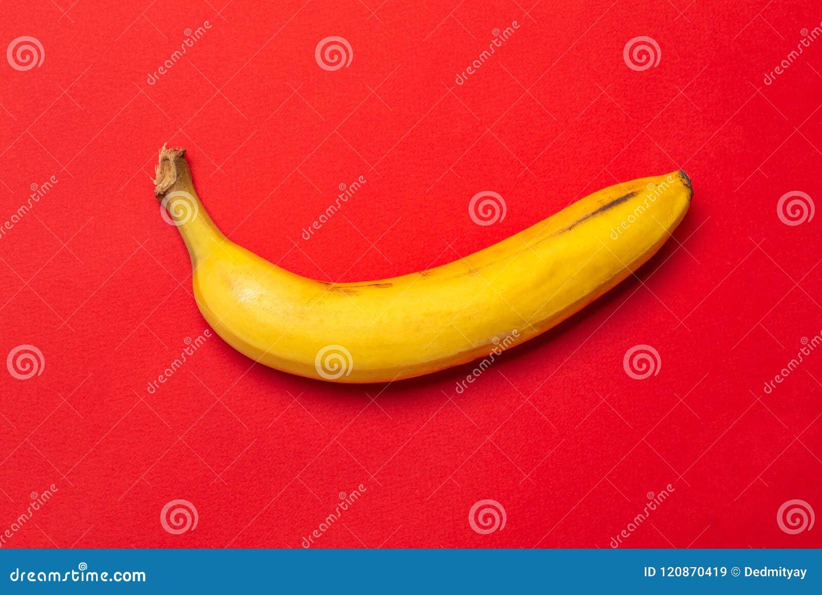 Żółty świeży dojrzały organicznie banan na czerwonym tle Nowożytny minimalny karmowy nadrealizmu pomysł dla projekta