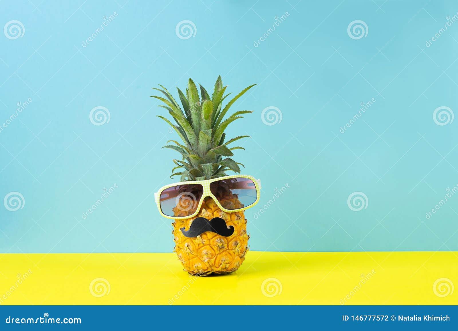 Żółty dojrzały ananas w okularach przeciwsłonecznych z czarnego wąsy żółtym błękitnym tłem Śmieszna twarz od tropikalnej owoc Poj