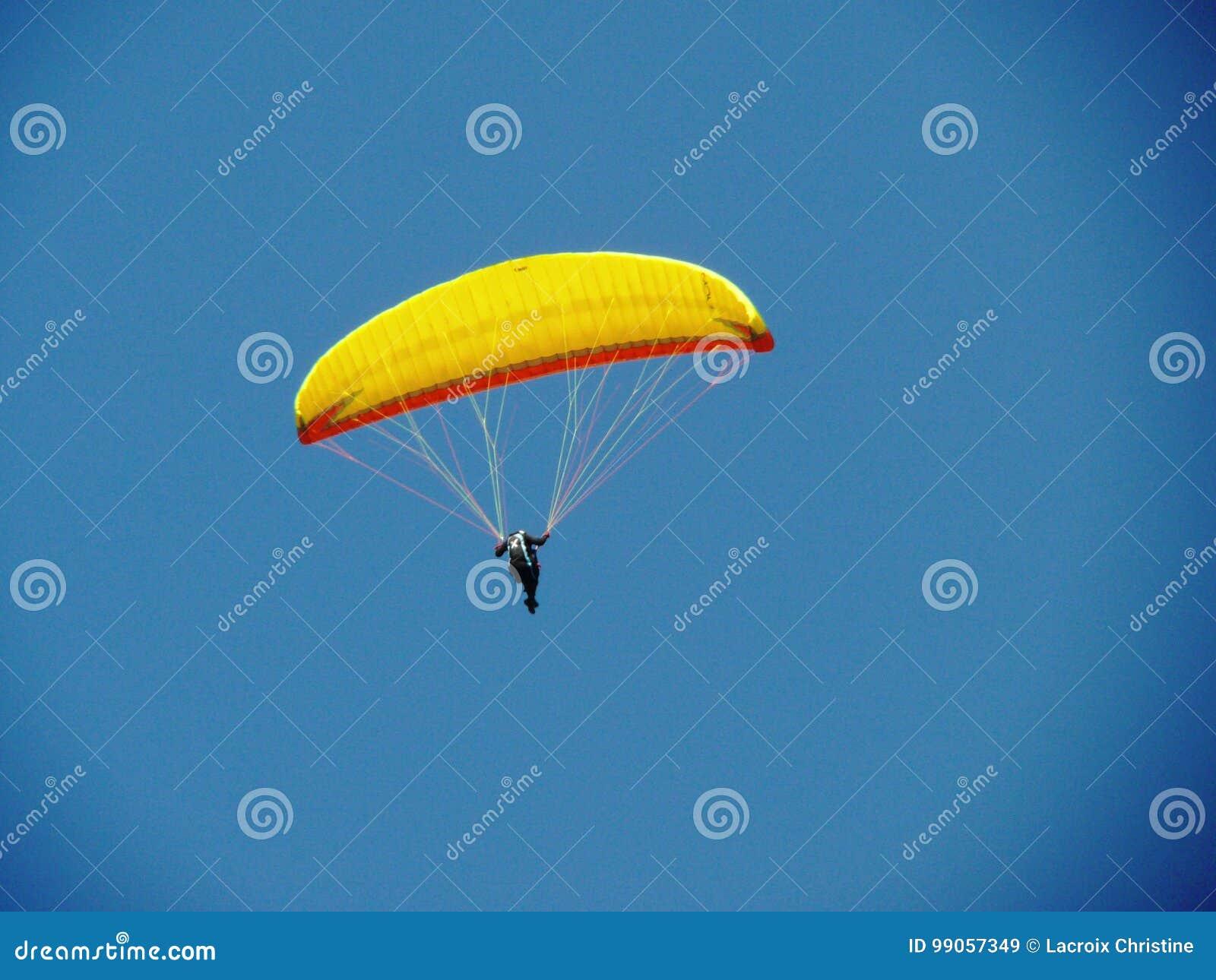 Żółty paraglider na niebieskim niebie
