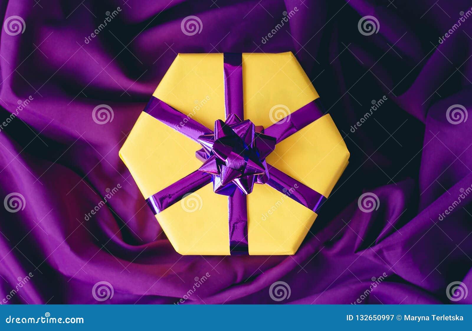 Żółty prezenta pudełko z purpurowym łękiem