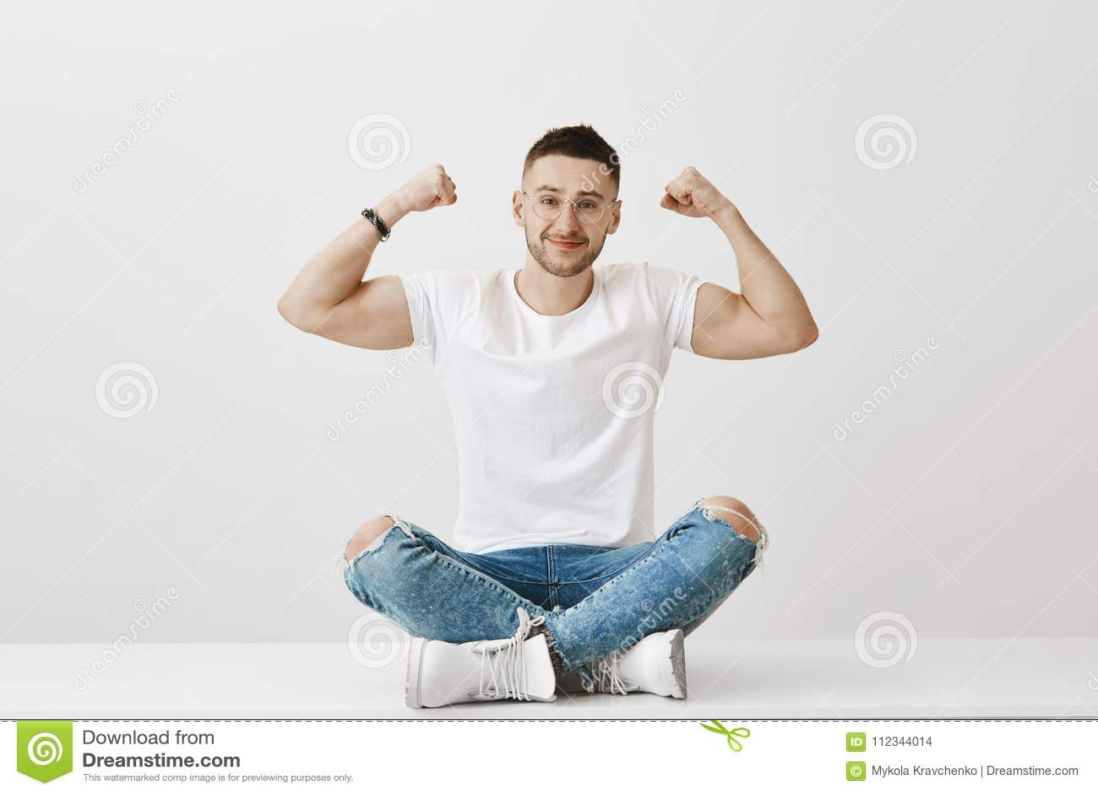 Żadny sterydów właśnie udziały wysiłek i władza wola Przyglądający silny mężczyzna siedzi na podłoga w szkłach podczas gdy pokazy