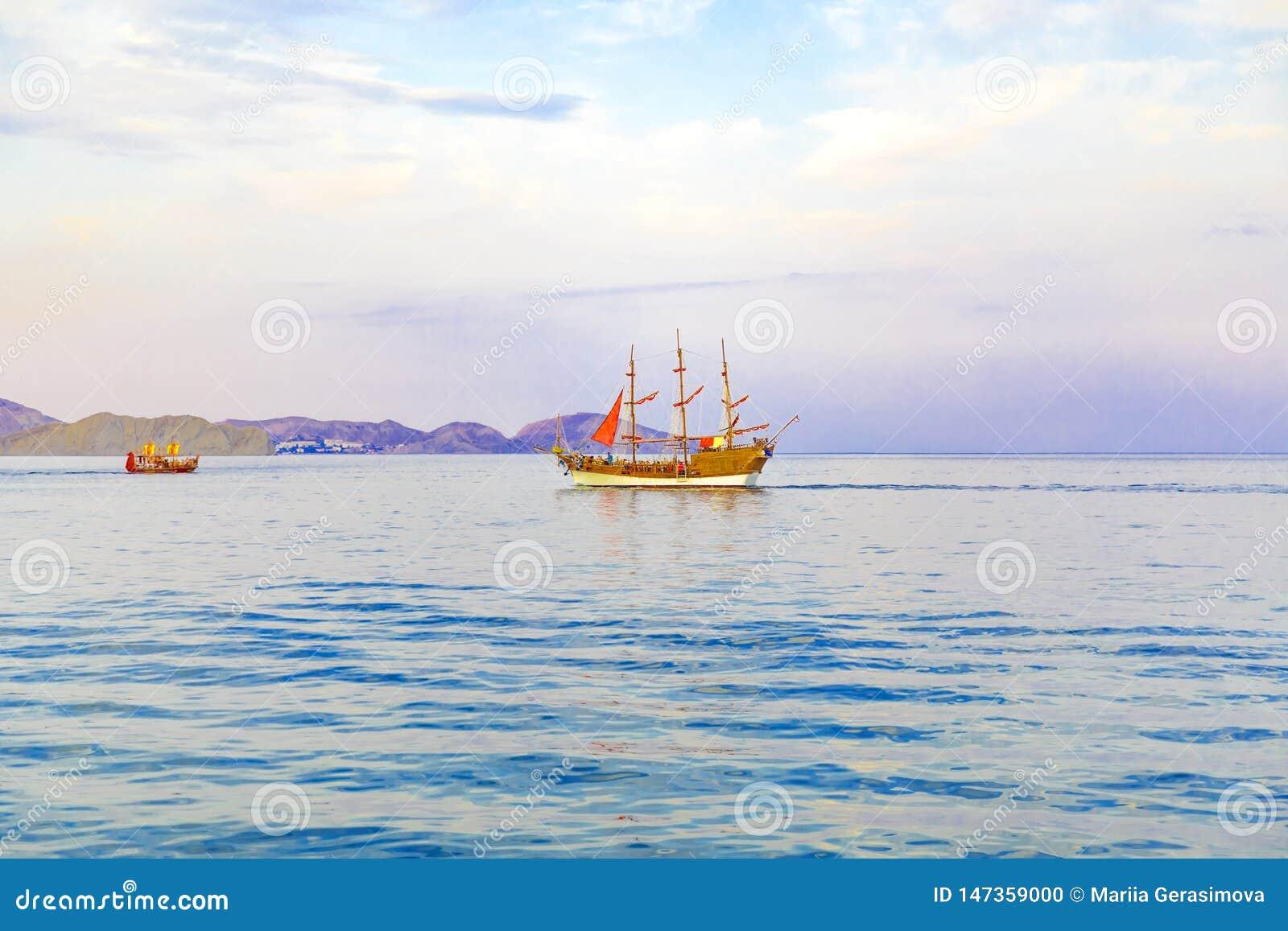 Żaglówka z szkarłatnymi żaglami na morzu iść brzeg