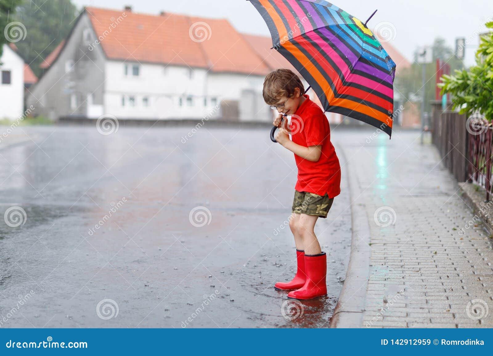 Żartuje chłopiec jest ubranym czerwonych podeszczowych buty i odprowadzenie z parasolem