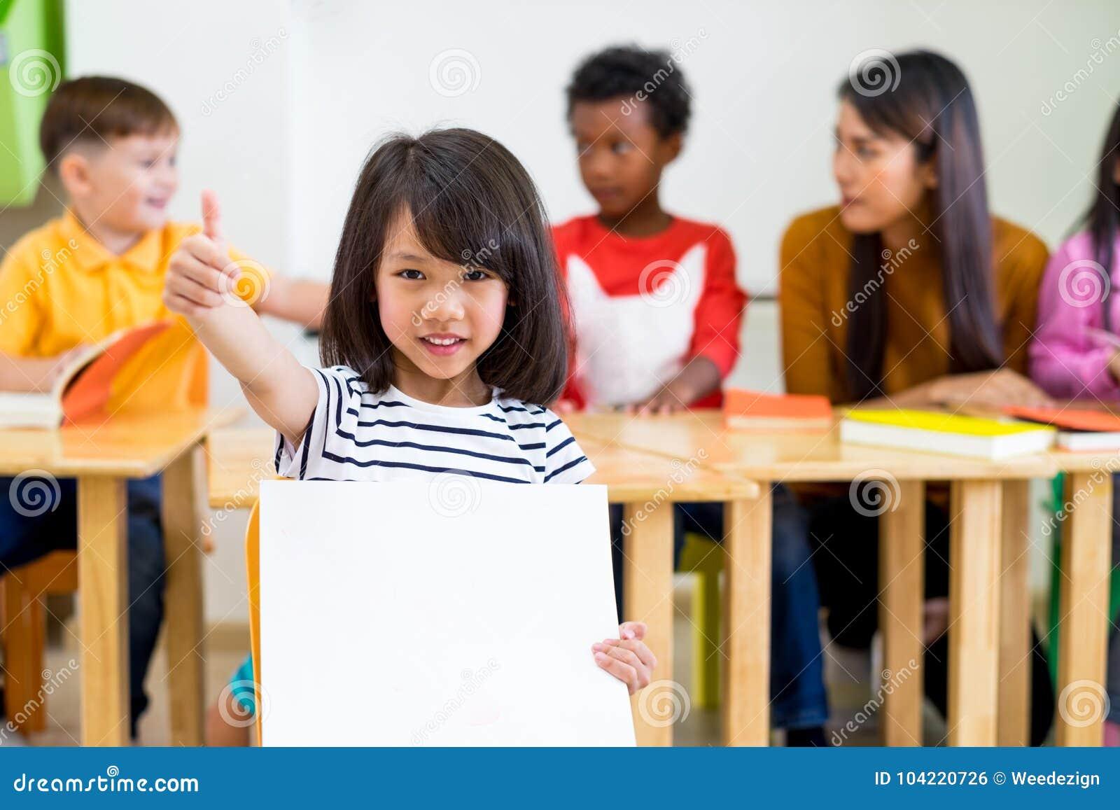 Żartuje dziewczyn aprobaty i mienie pustego białego plakat z różnorodnością