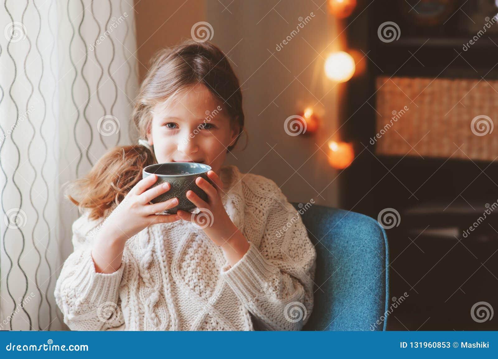 Żartuje dziewczyny pije gorącego kakao w zima weekendzie w domu, siedzi na wygodnym krześle