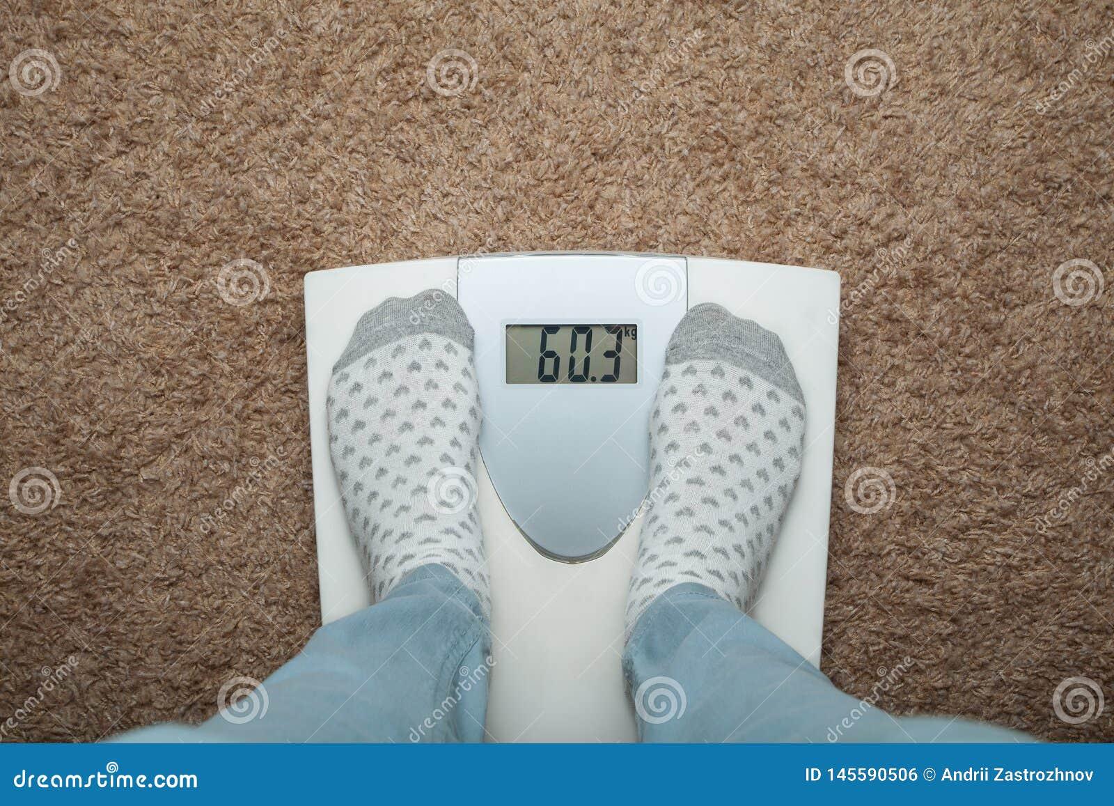 Żeńscy cieki w skarpetach na elektronicznych skalach Nadmierny ciężar i dieta