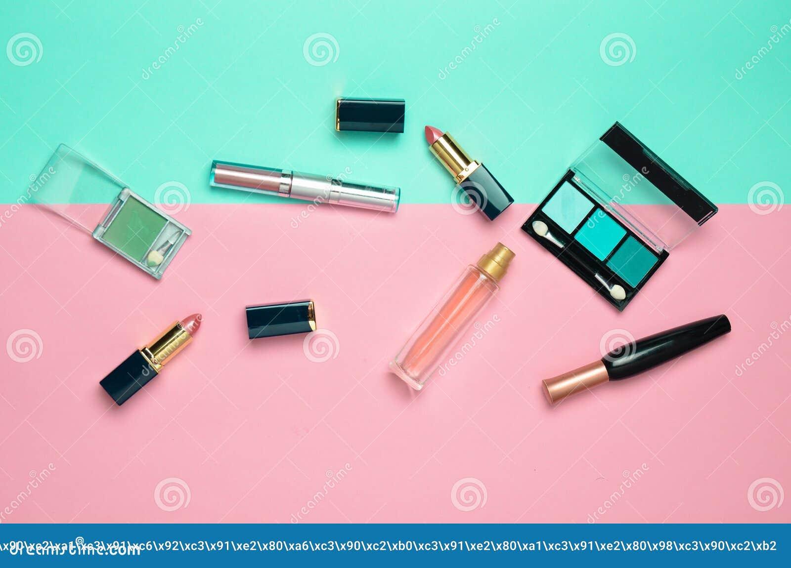 Żeńscy kosmetyki dla makijażu układu na pastelowym tle Kosmetyk ocienia, makijażu muśnięcie, eyeshadow pomadka, pachnidło butelka