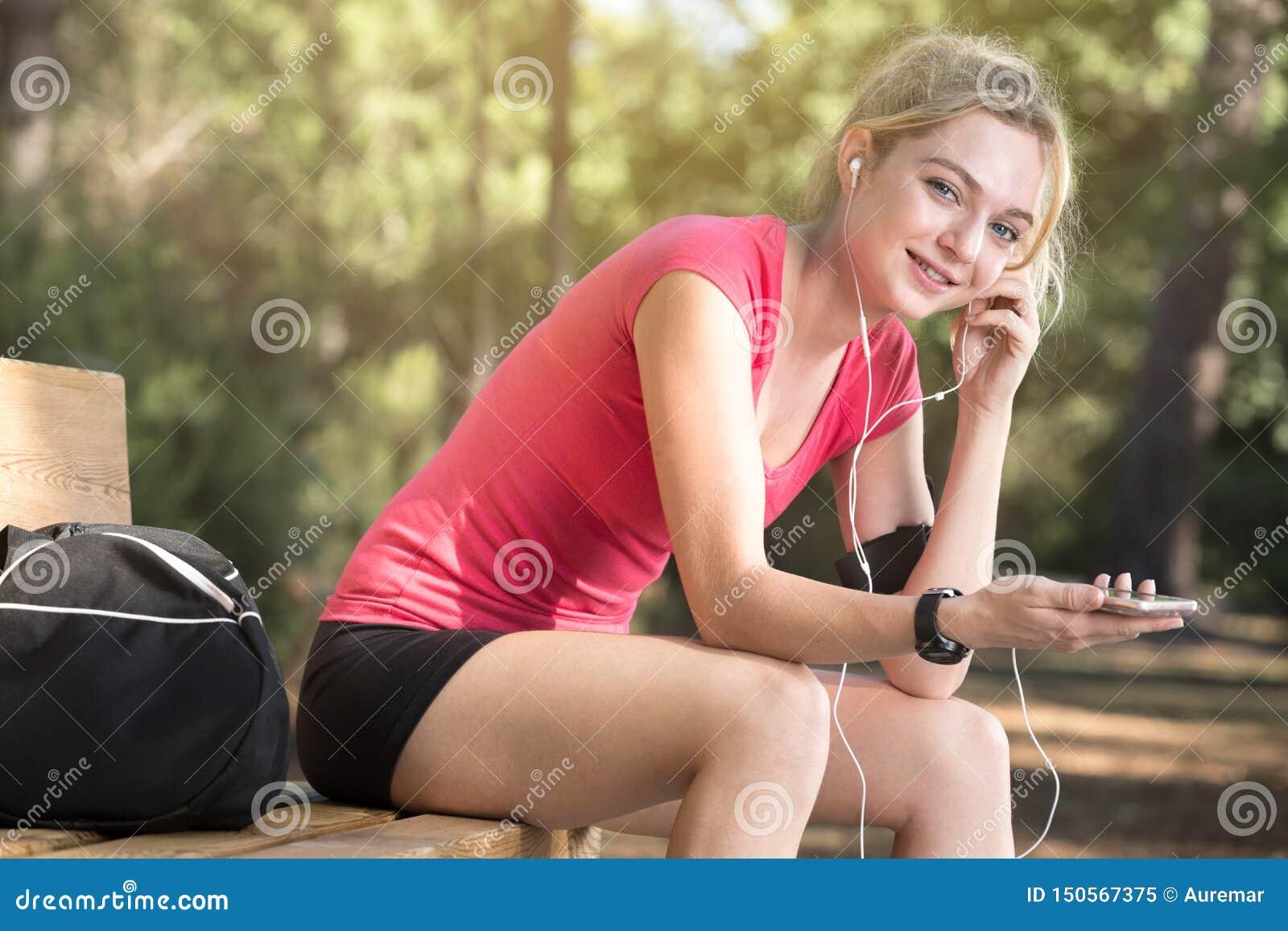 Żeńska atleta siedzi na ławce z hełmofonami