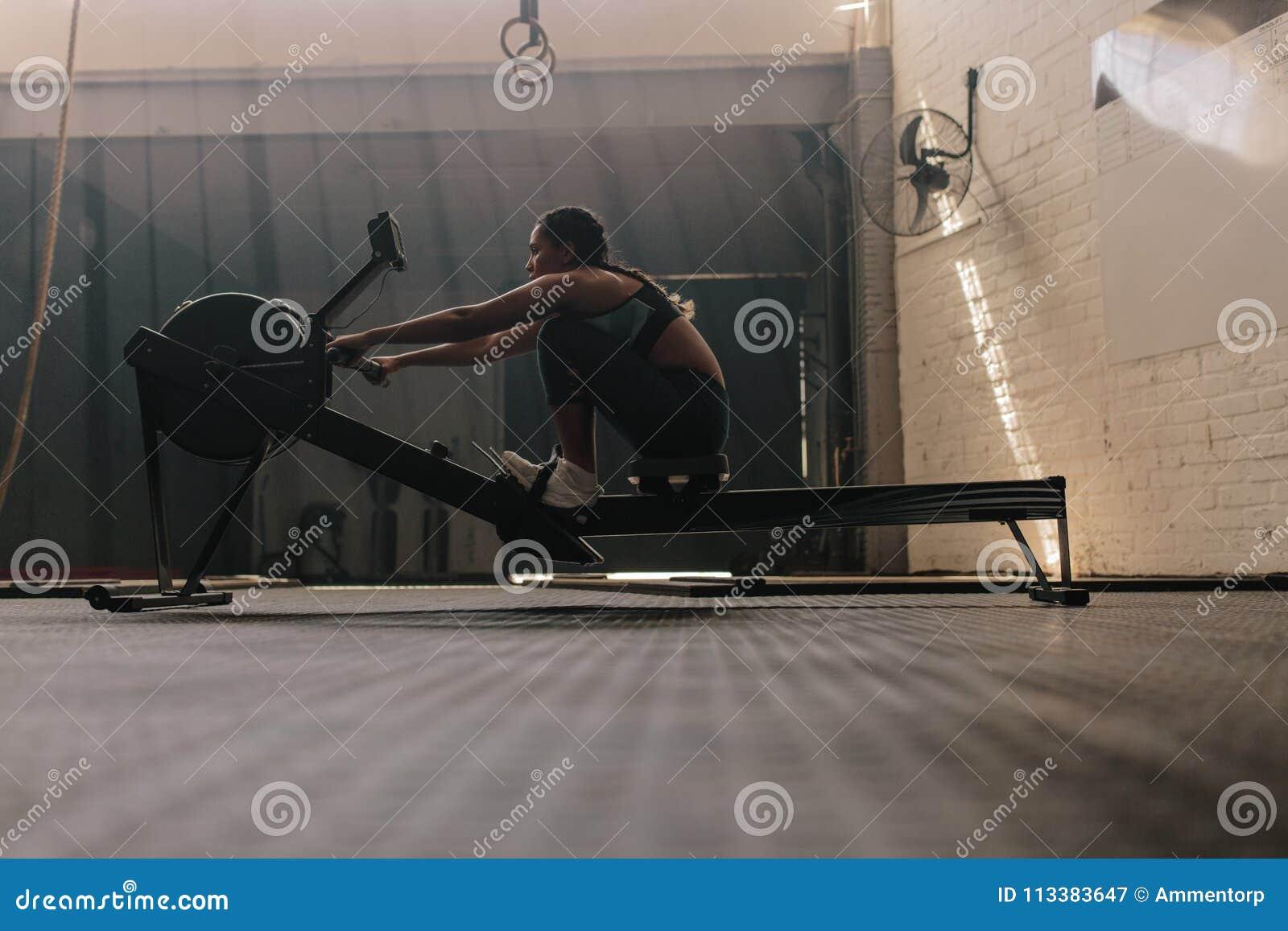 Żeńska atleta używa wioślarską maszynę