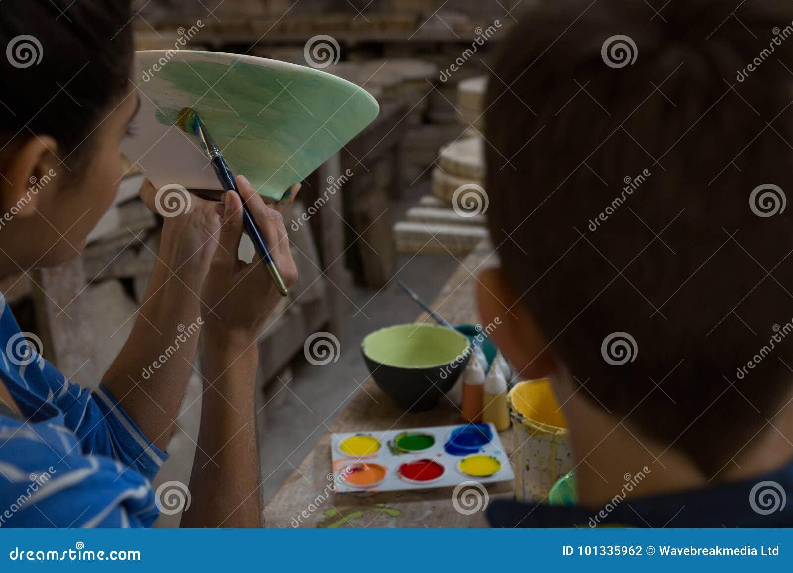 Żeńska garncarka pomaga jej syna w malować puchar