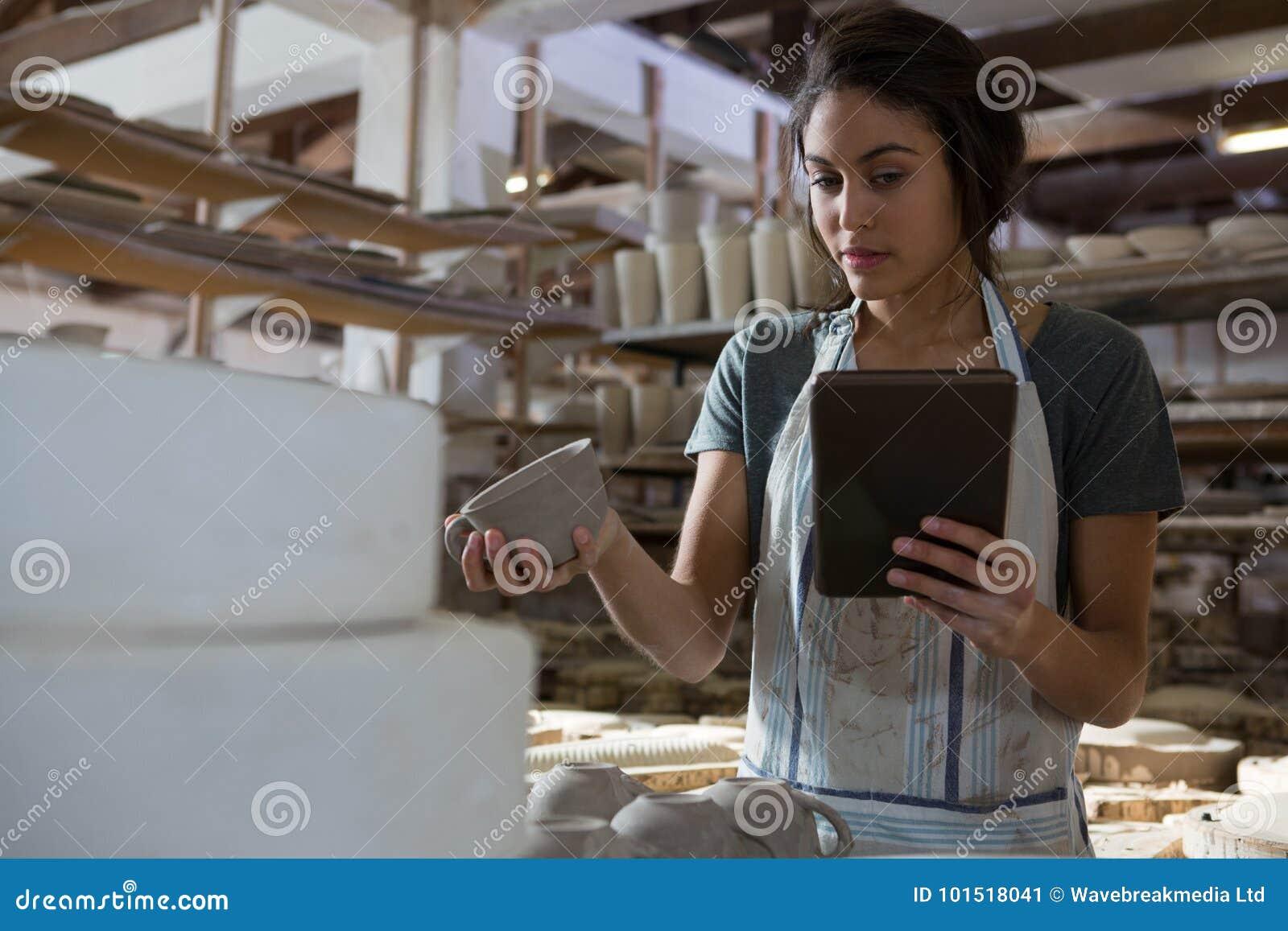 Żeńska garncarka trzyma filiżankę podczas gdy używać cyfrową pastylkę