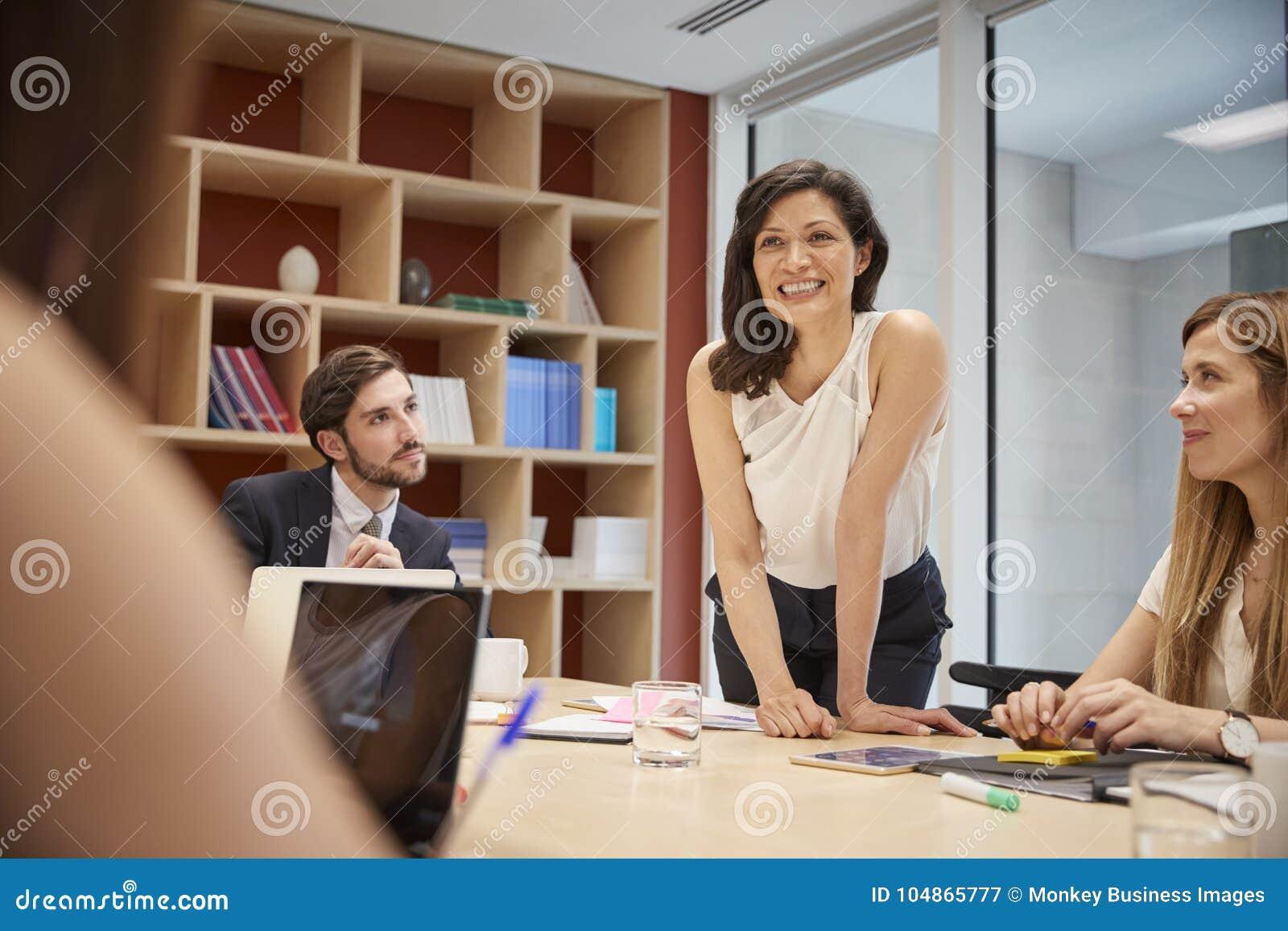Żeńska kierownik pozycja przy sala posiedzeń spotkaniem, zamyka up