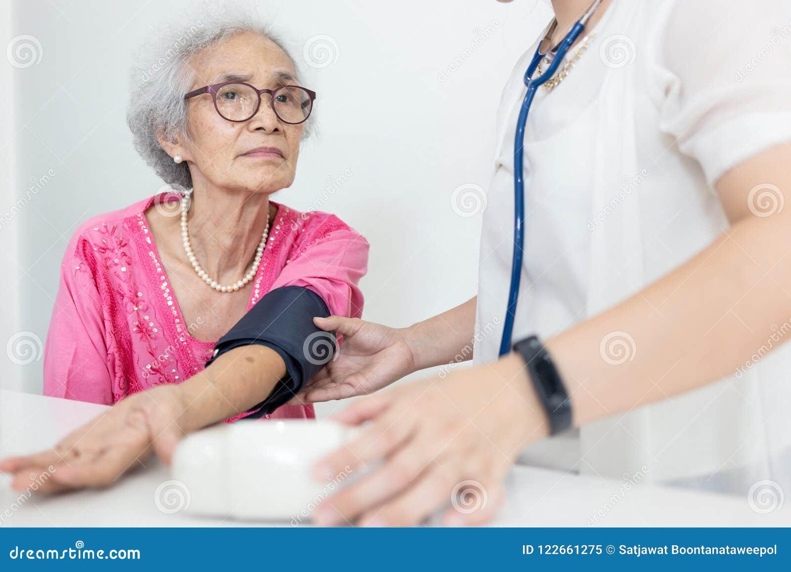 Żeńska pielęgniarka sprawdza ciśnienie krwi starsza kobieta w domu, H