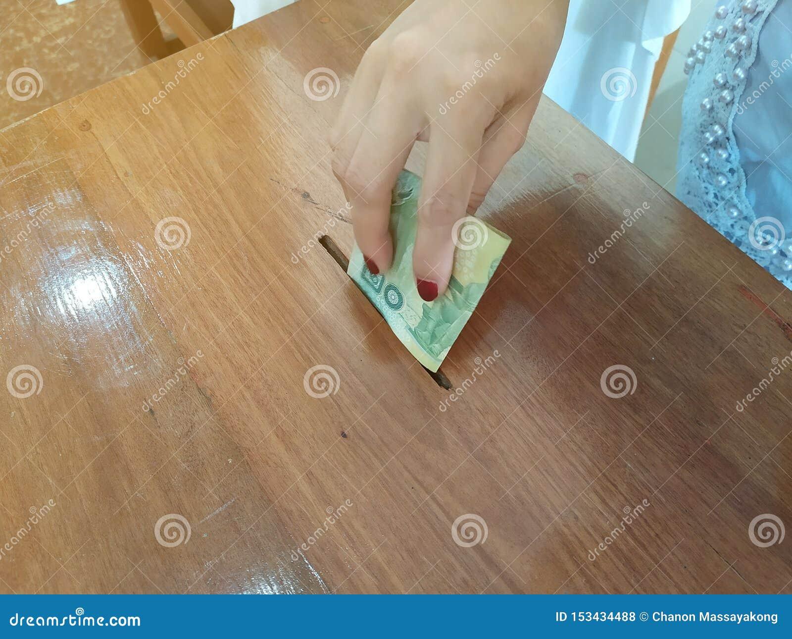 Żeńska ręka stawiający tajlandzki pieniądze w drewna pudełku