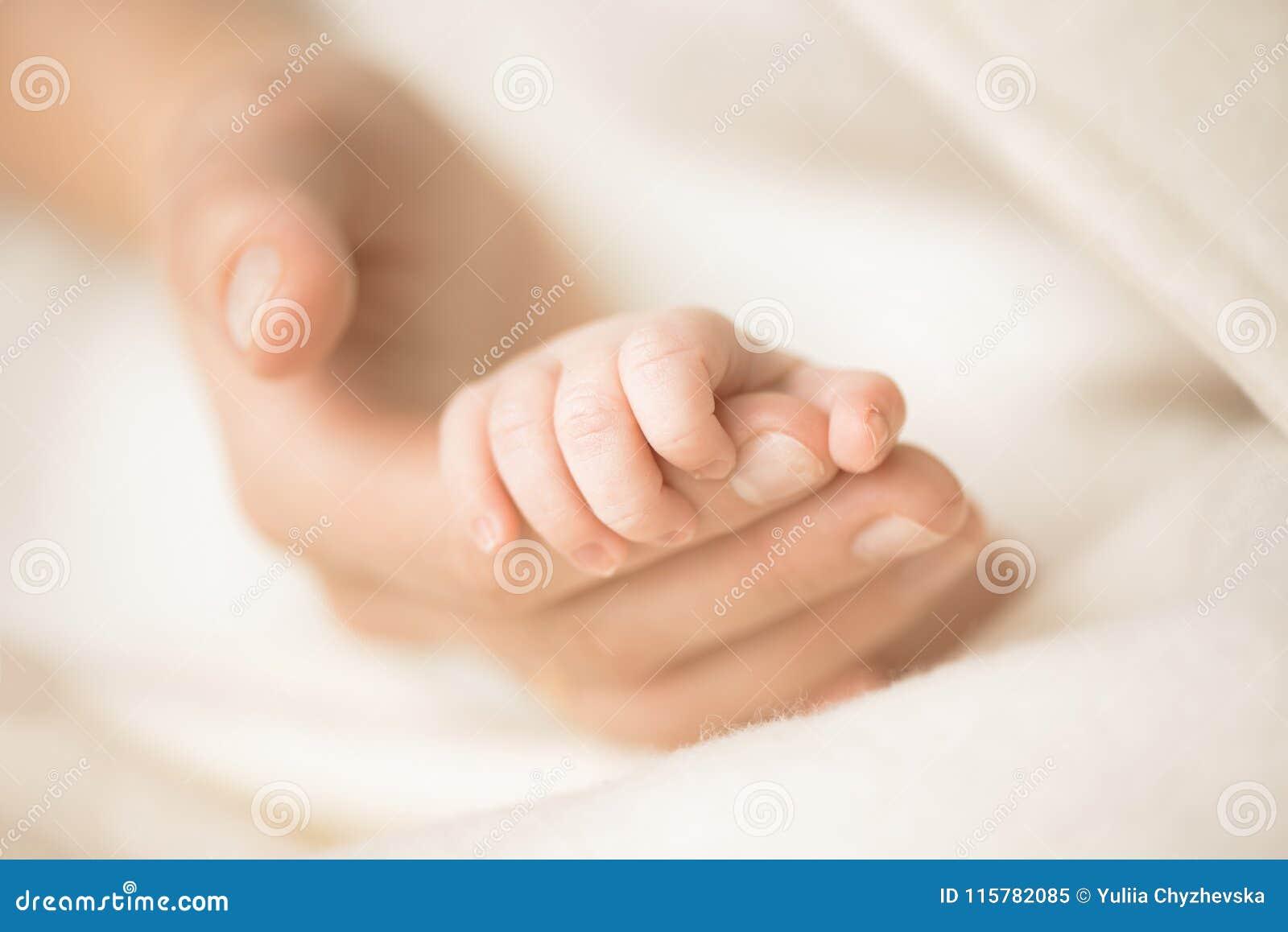 Żeńska ręka trzyma jej nowonarodzoną dziecka ` s rękę Mama z jej dzieckiem Macierzyński, rodzinny, narodziny pojęcie Odbitkowa pr