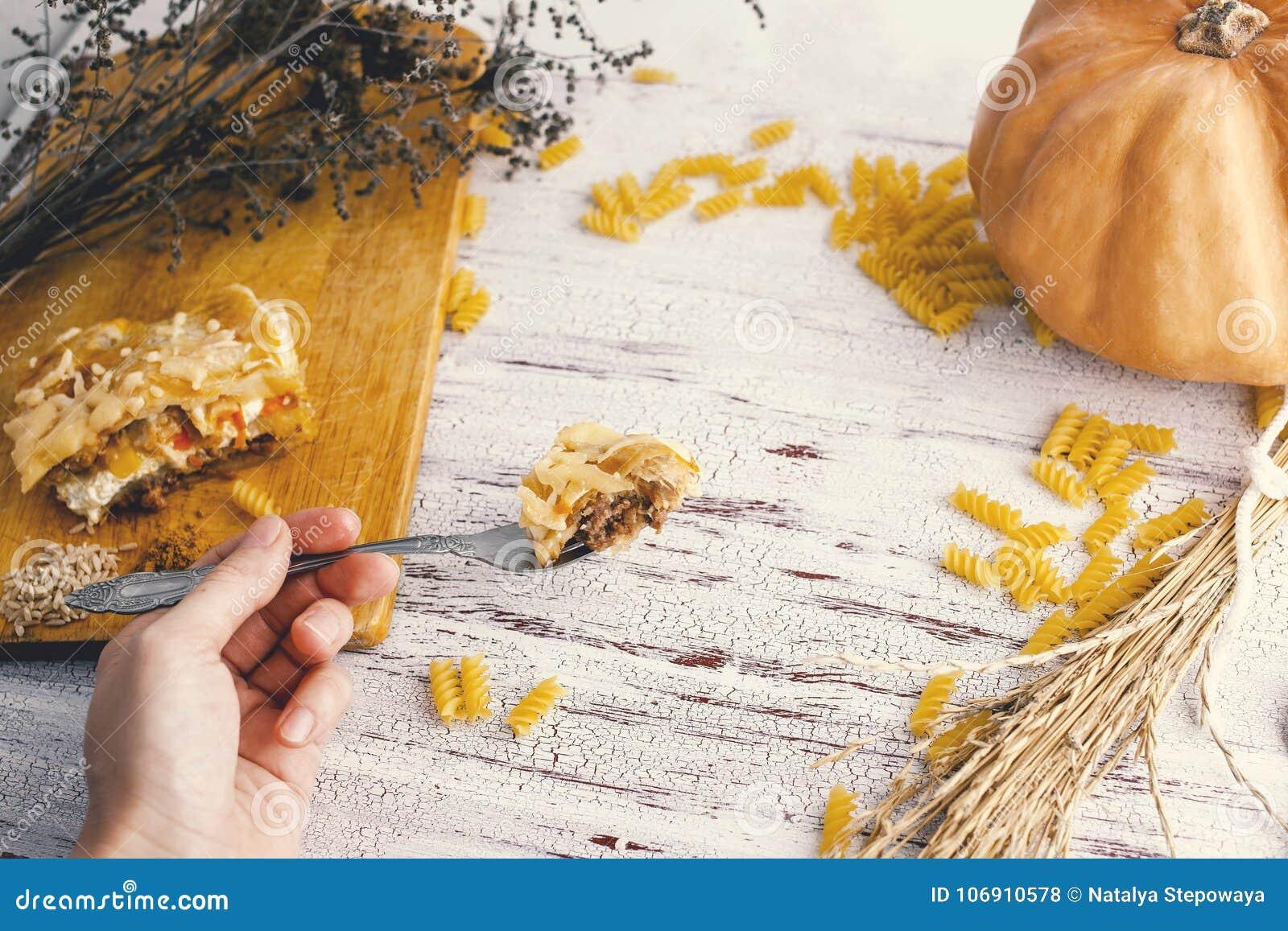 Żeńska ręka trzyma rozwidlenie z jedzeniem na białym tle stół