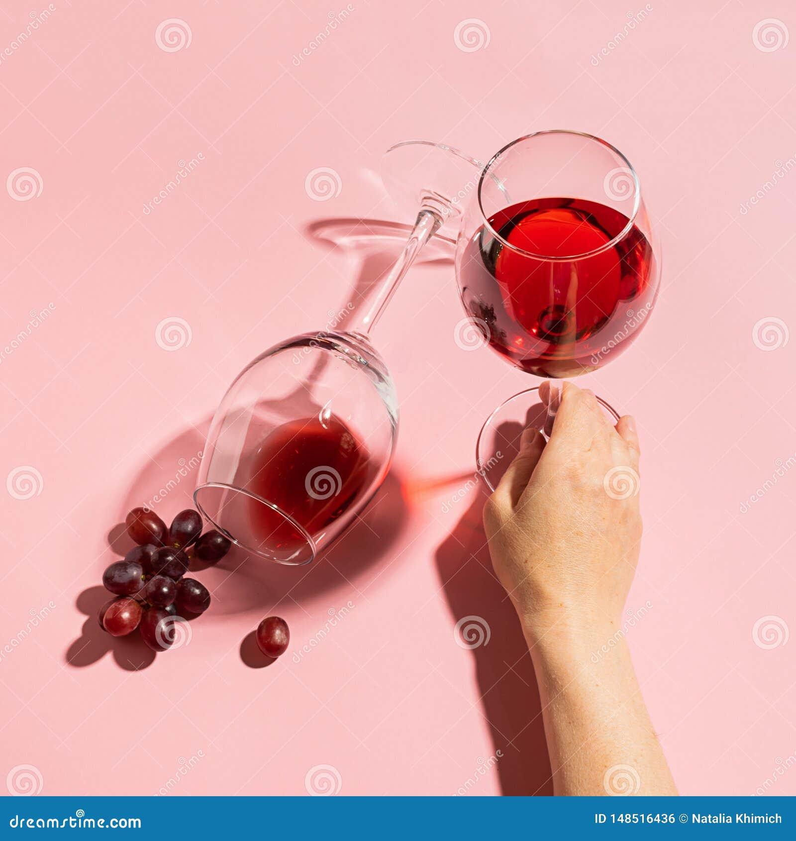 Żeńska ręka trzyma szkło z czerwonym winem i wiązką winogrona na delikatnym różowym tle Selekcyjna ostro?? minimalista