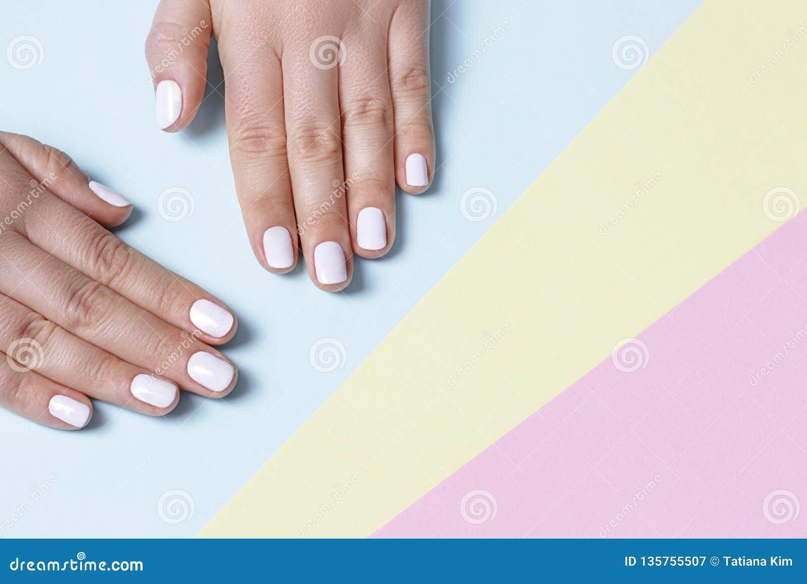 Żeńska ręka z białym manicure em na trykotowym tle z kopii przestrzenią, odgórny widok