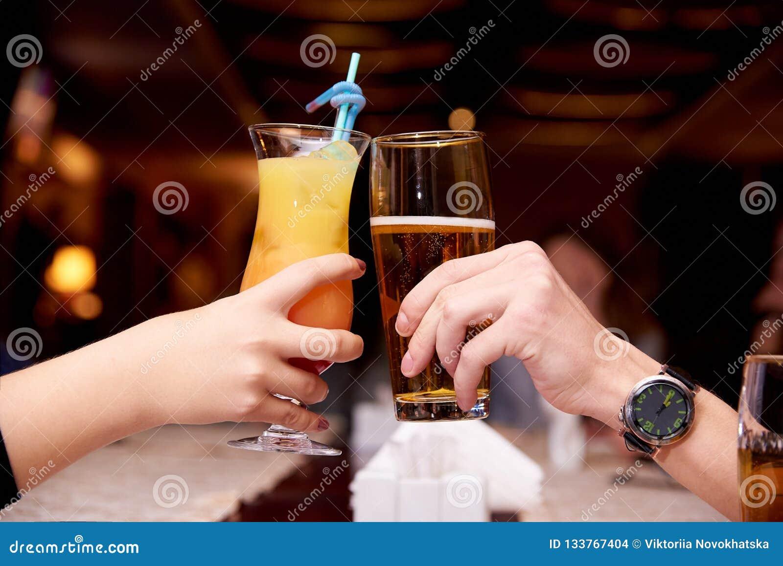Żeńska ręka z koktajlem i męska ręka z piwem