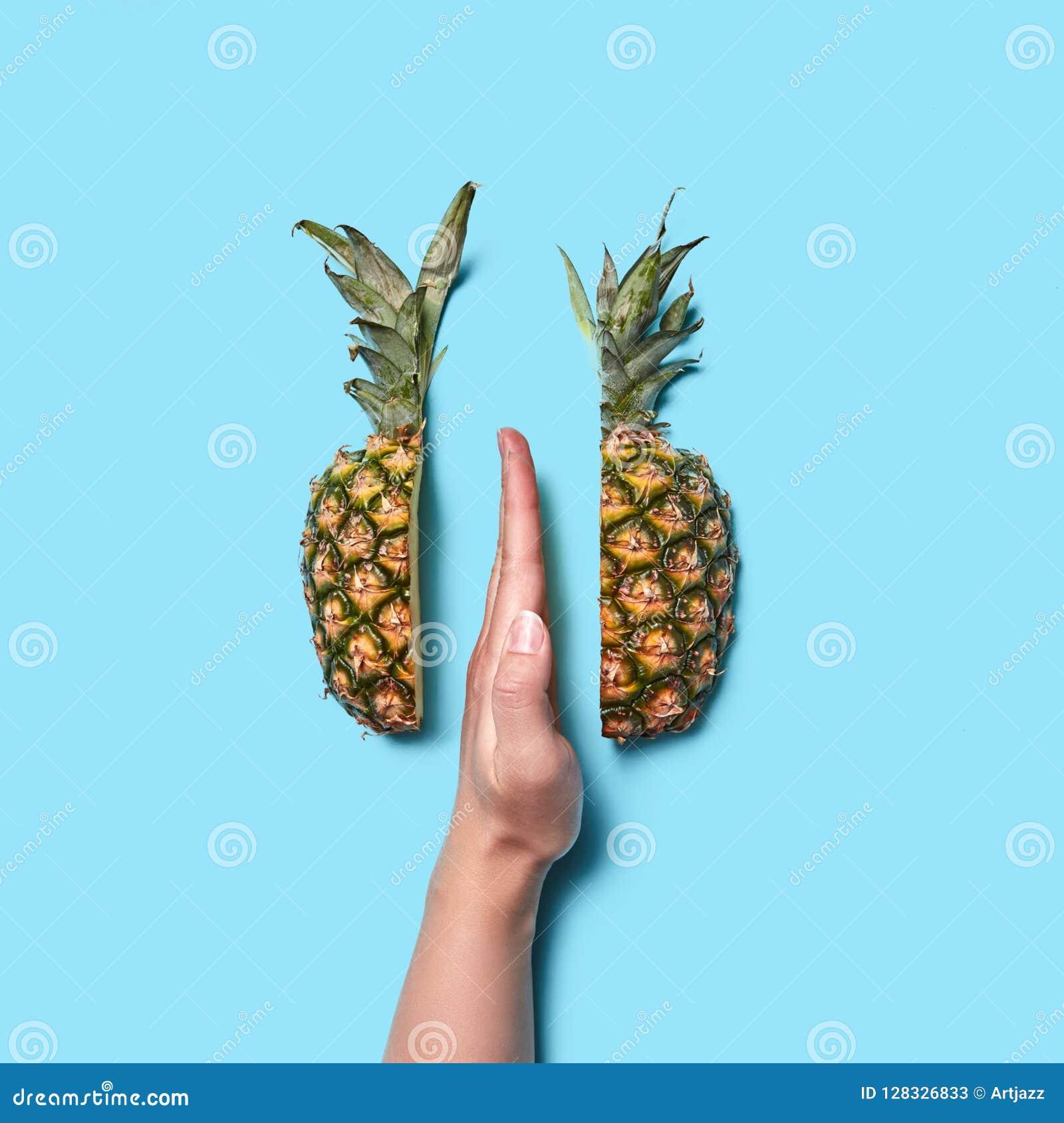 Żeńska ręki część z palcową połówką ananas na błękitnym tle z przestrzenią dla teksta Mieszkanie nieatutowy