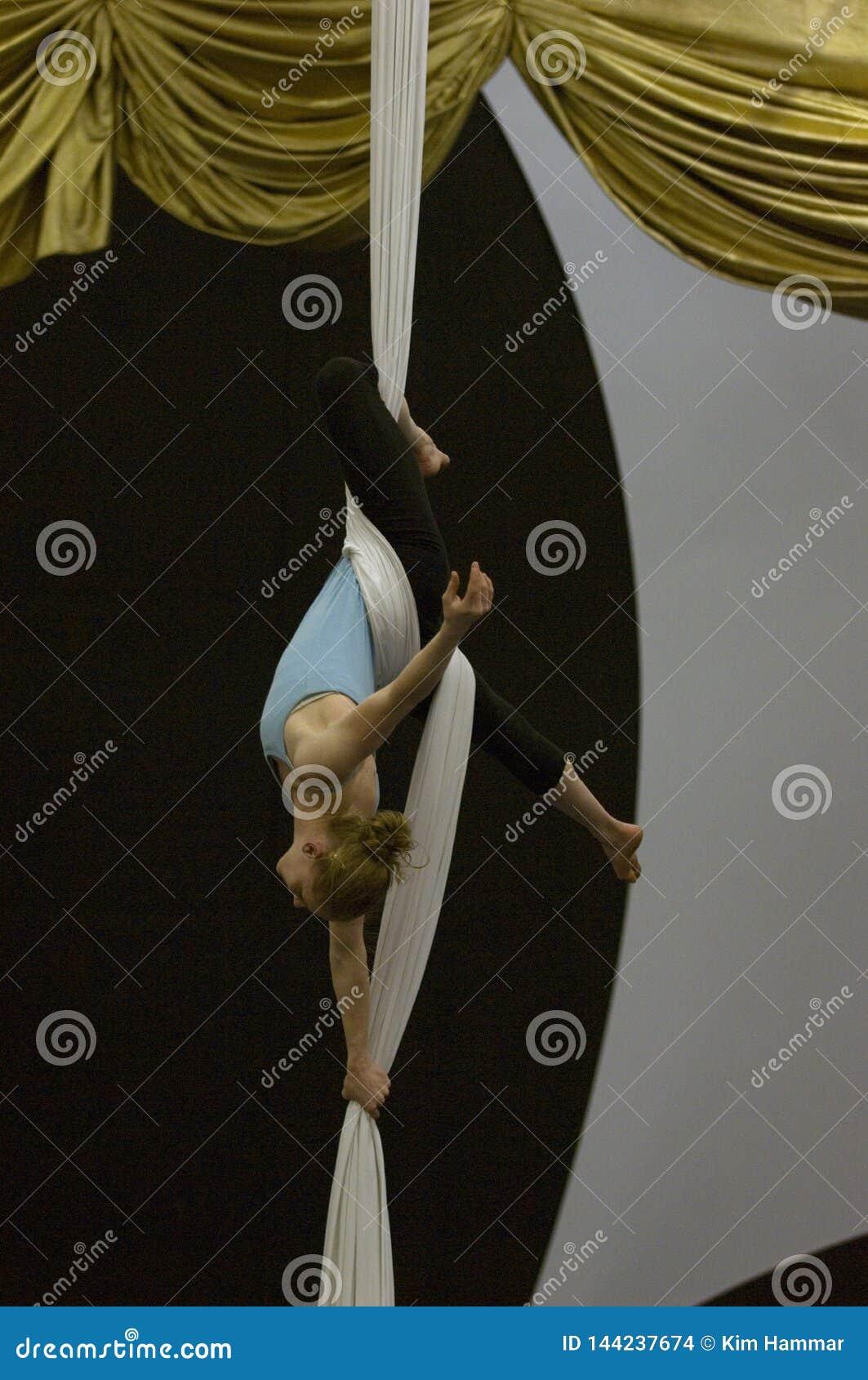 Żeński akrobata ono zawiesza i iść na piechotę góra używać powietrznych jedwabie wokoło jej talii