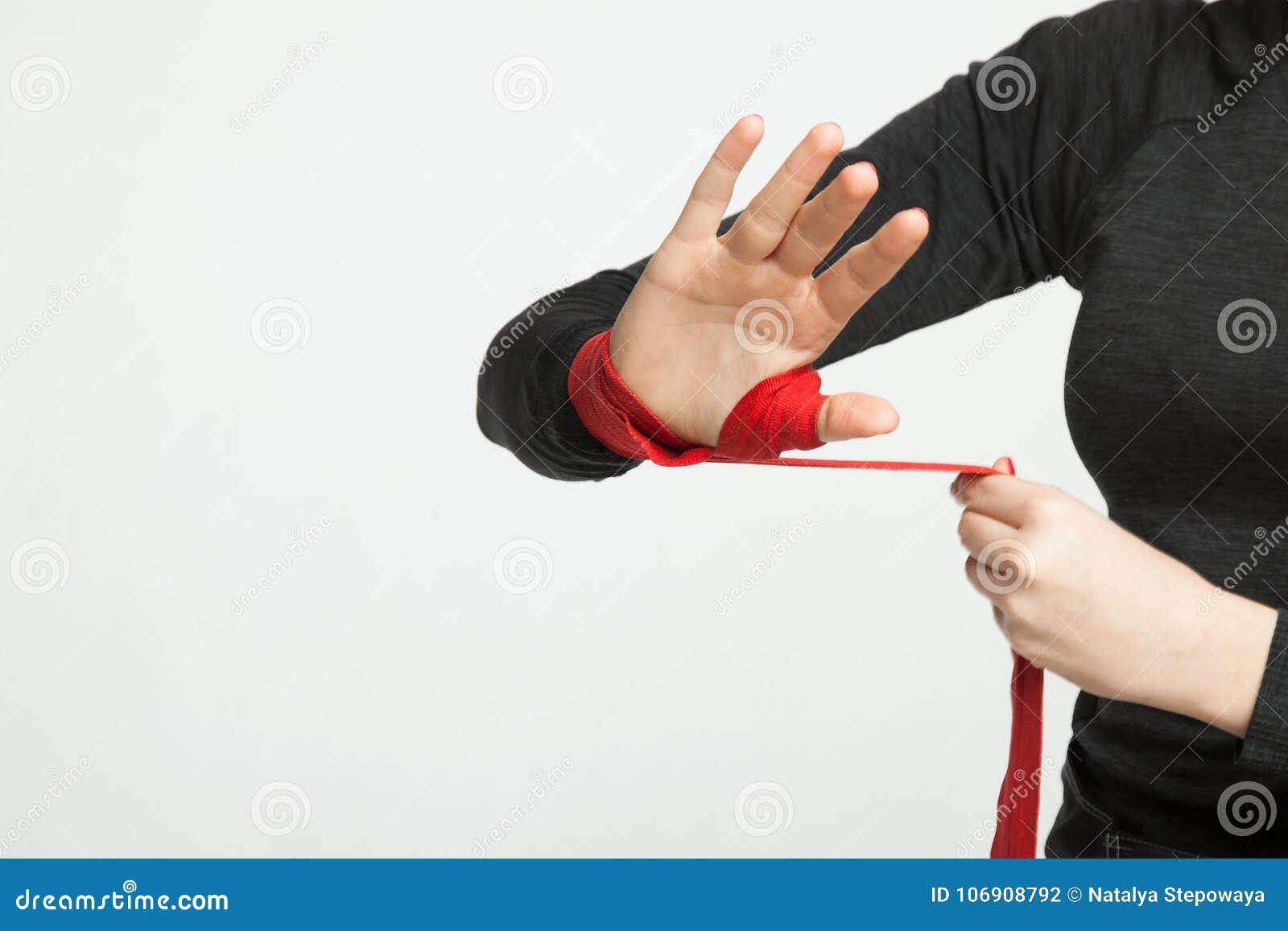 Żeński bokser zawija ręki z czerwonymi boks opakunkami na Białym tle z przestrzenią dla teksta