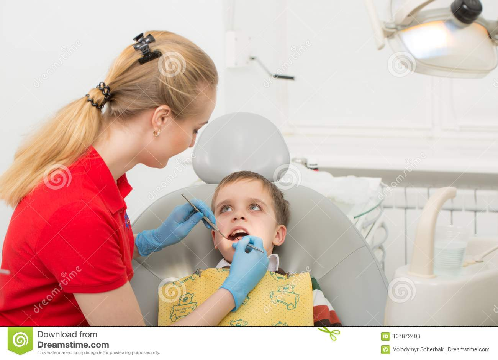 Żeński dentysta egzamininuje zęby cierpliwy dziecko dziecka usta szeroko otwarty w dentysty ` s krześle Zakończenie