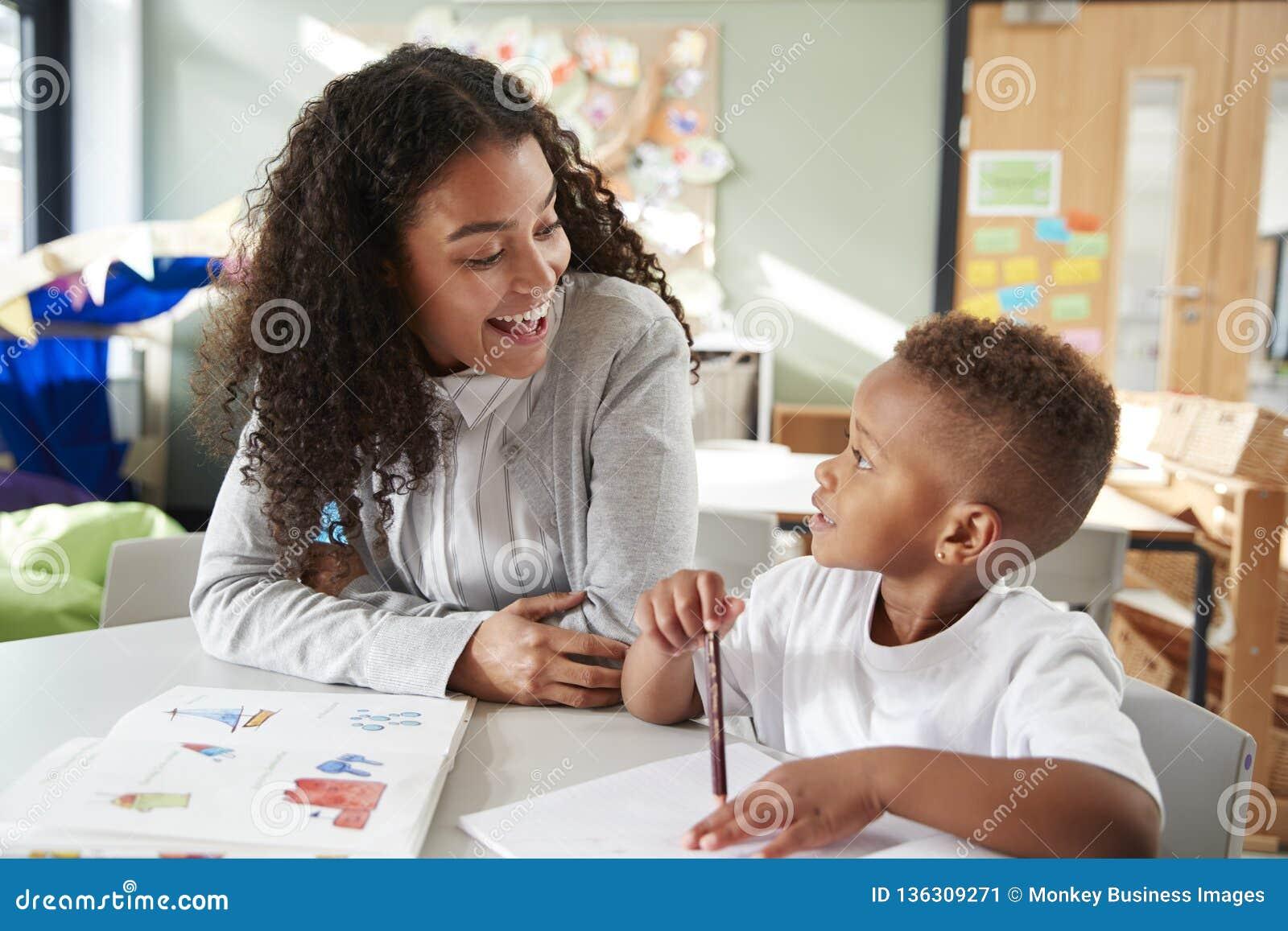 Żeński dziecięcy nauczyciel pracuje jeden na jeden z młodym uczniem, siedzi przy stołem ono uśmiecha się przy each inny, zakończe