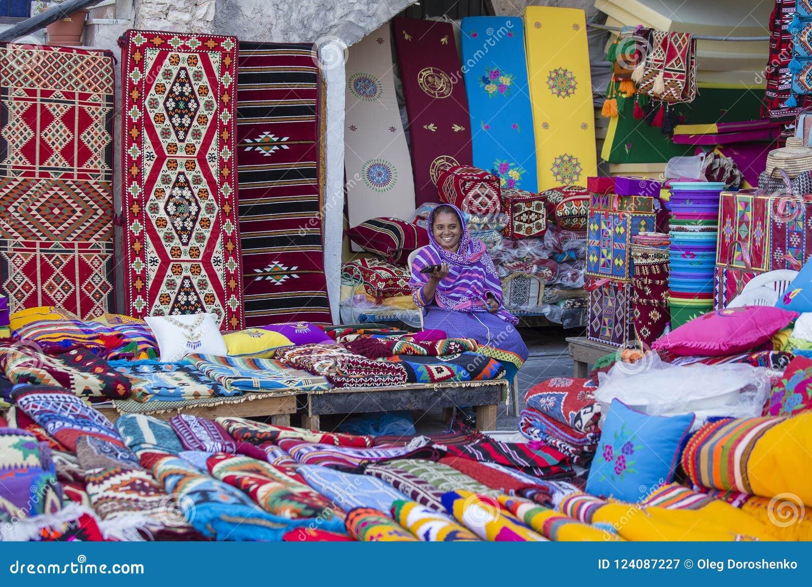 Żeński handlowiec przy Souq Waqif rynkiem w Doha, z multicolour dywanami, kilimami i innymi rzeczami, Qatar dauhańskiej