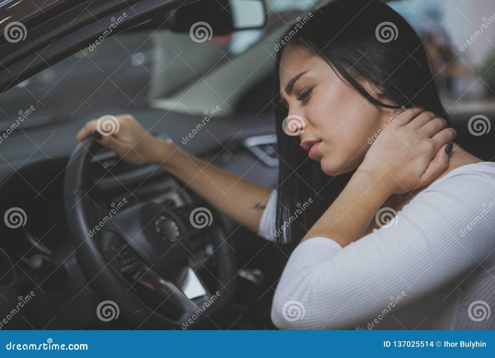 Żeński kierowca naciera jej bolącą szyję po długiej przejażdżki