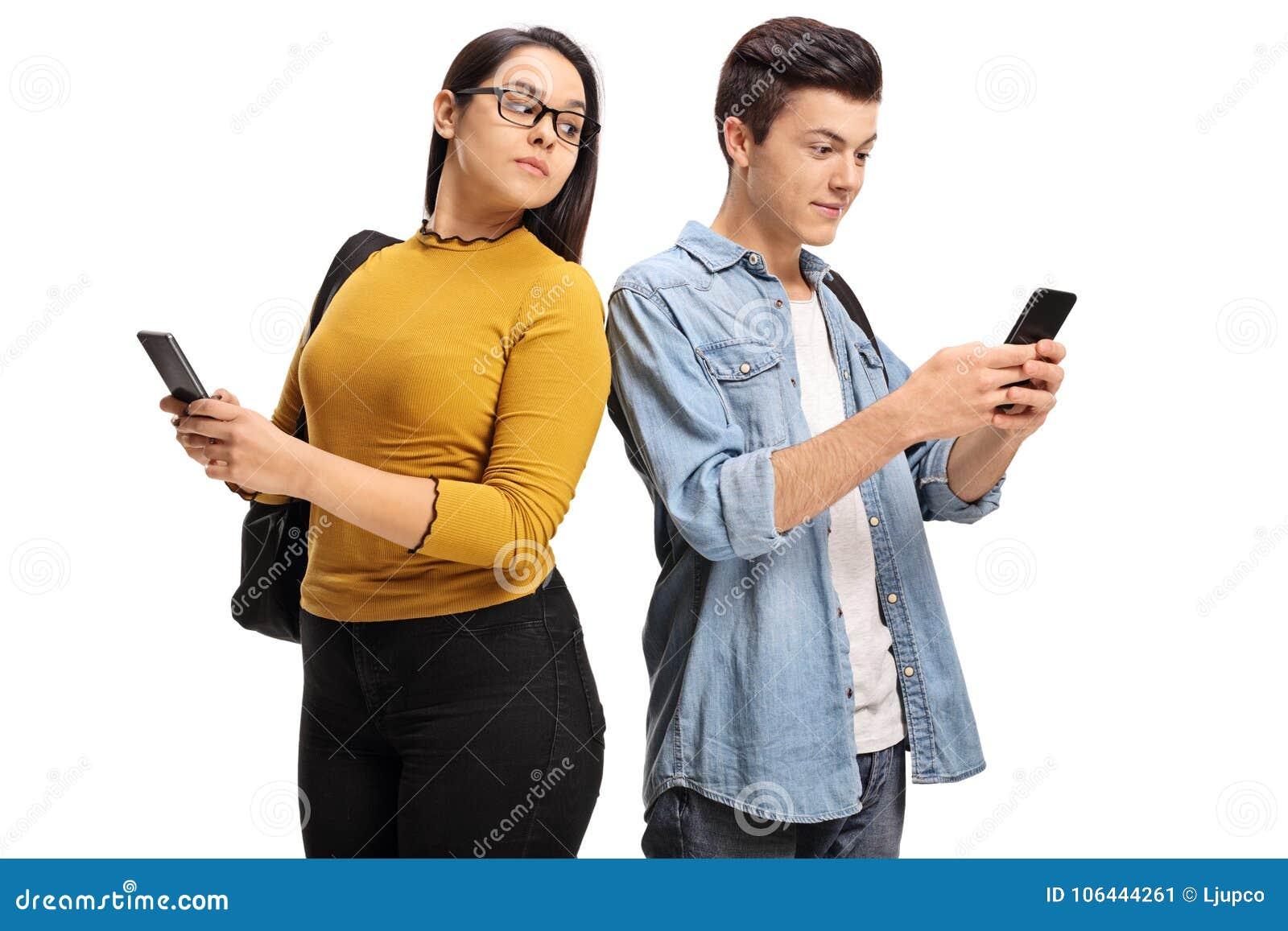 Żeński nastoletni studencki zerkanie przy telefonem męski nastoletni uczeń
