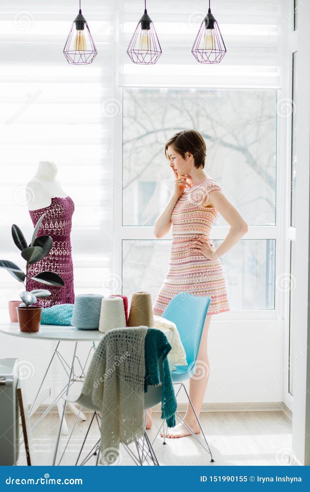 Żeński projektanta główkowanie podczas gdy pracujący z trykotową suknią w wygodnym pracownianym wewnętrznym, freelance styl życia